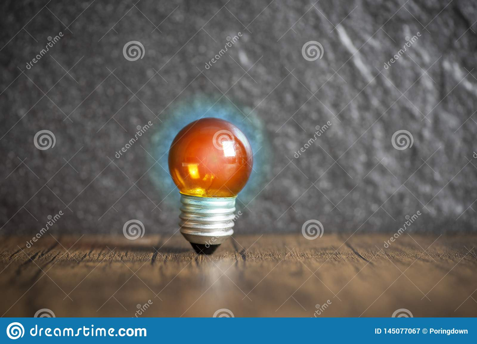 idea concept with orange light bulb and blue light wooden with dark background