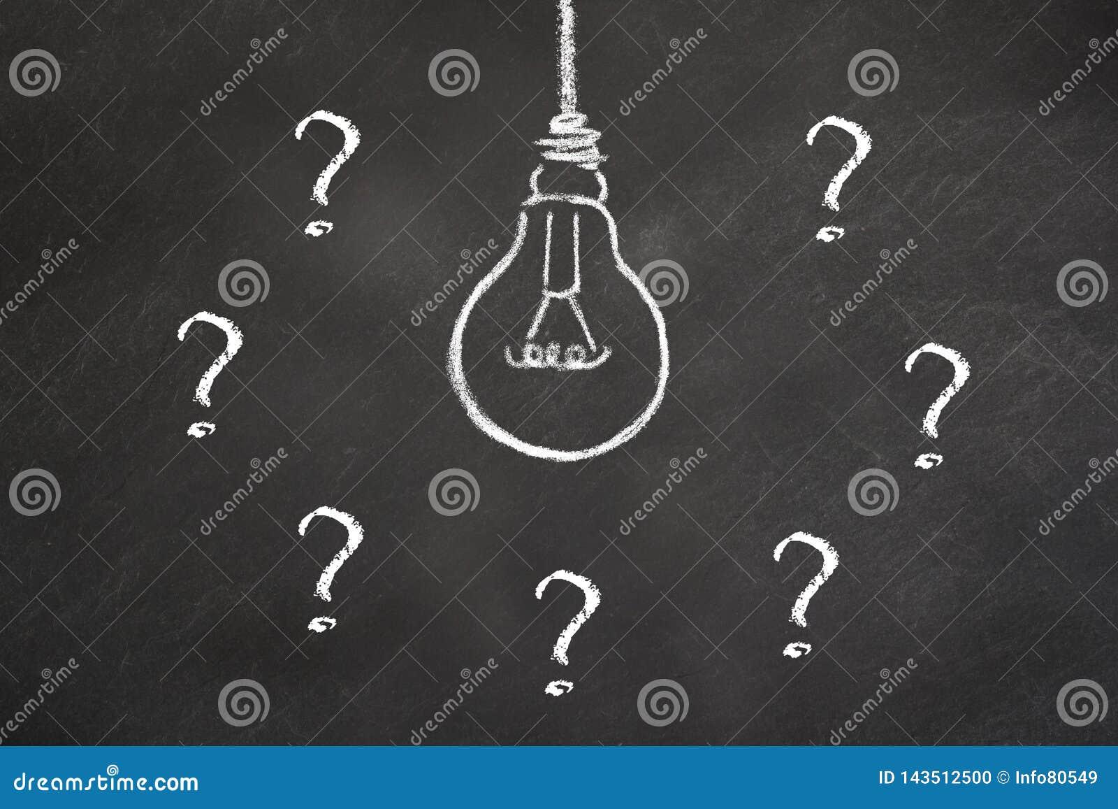 Idea del bulbo de la tiza con los signos de interrogación en una pizarra