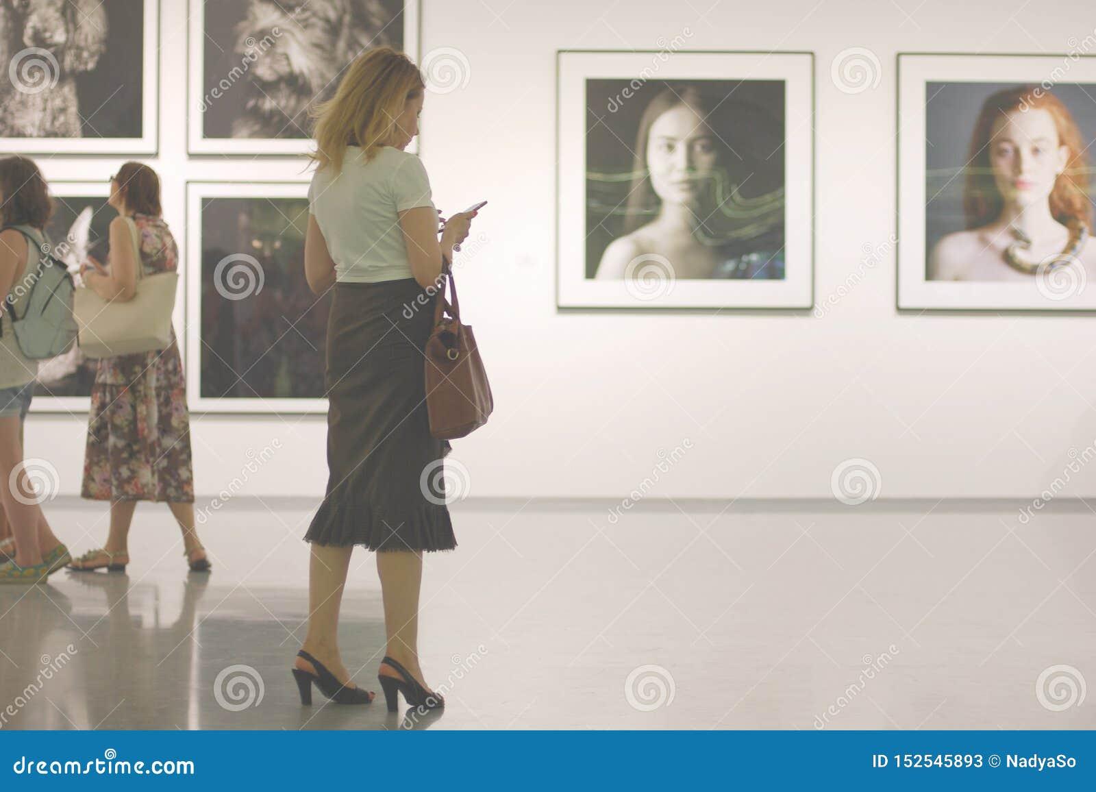 Idea di dipendenza del telefono cellulare La donna in galleria di foto non ascolta ma per mezzo del suo smartphone