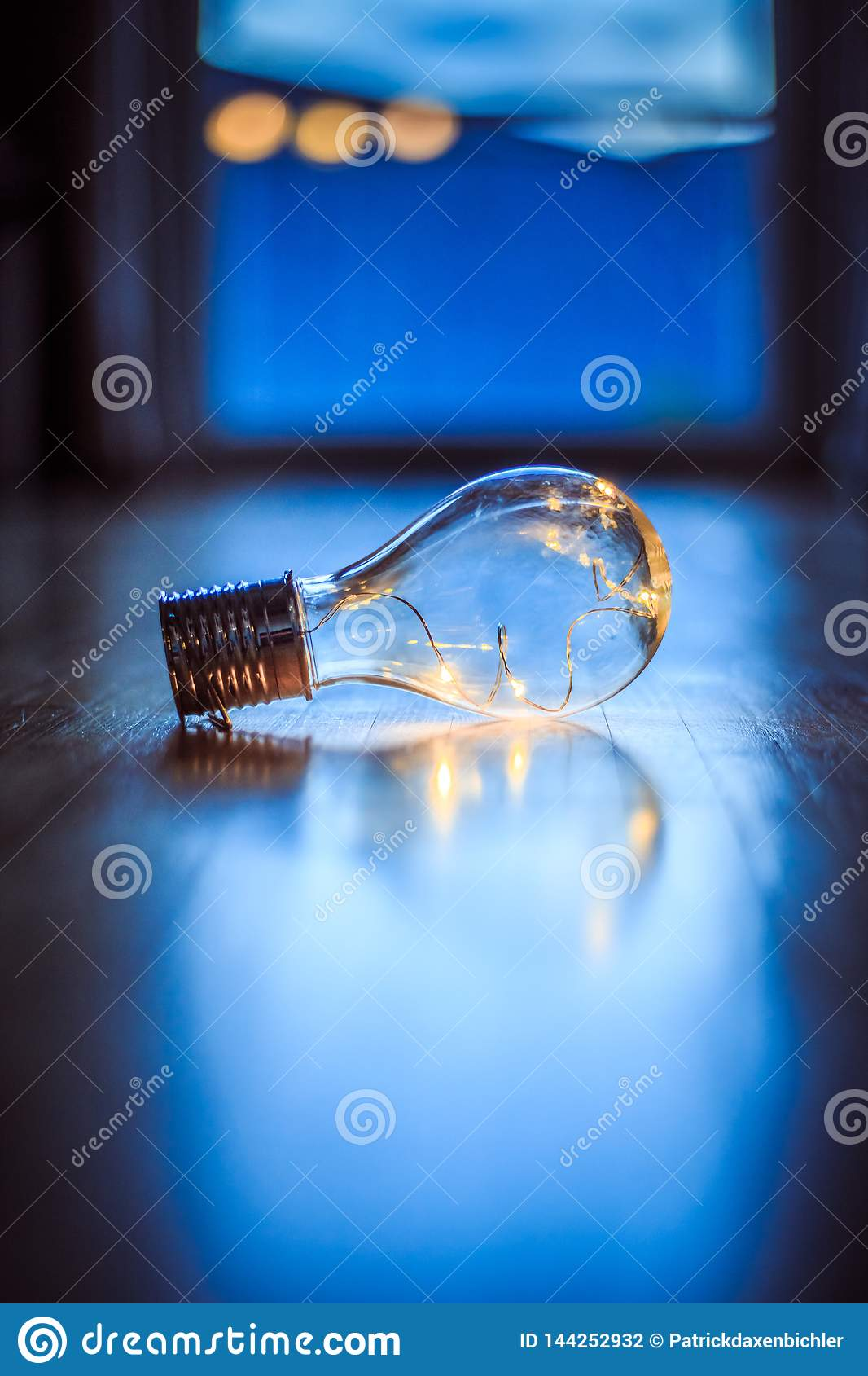 Ideas and innovation: Light bulb with LEDs is lying on the wooden floor. Window and light in the blurry background