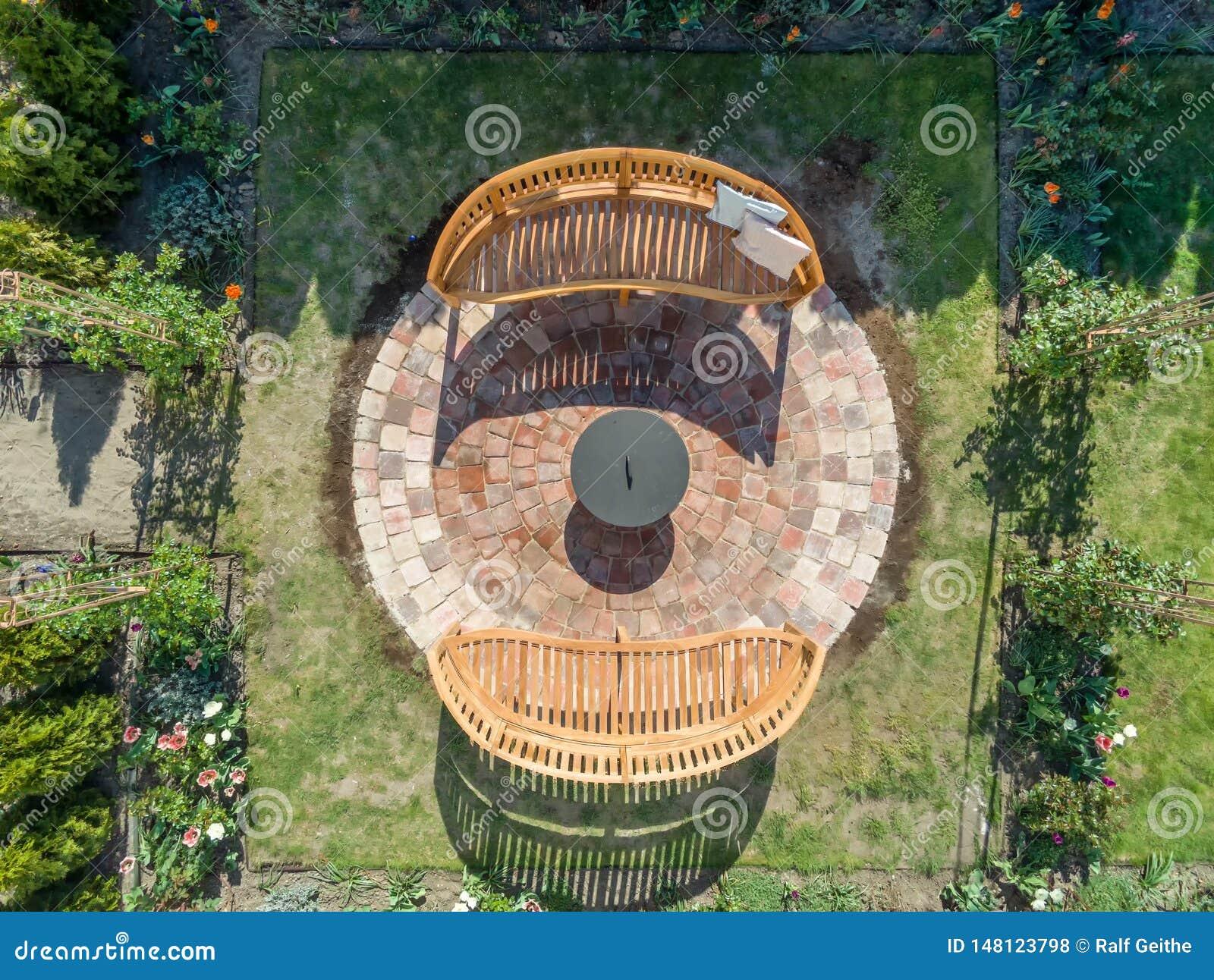 Ideia aérea de uma área pavimentada com os dois bancos de madeira acolhedores e uma bacia de fogo em seu próprio jardim