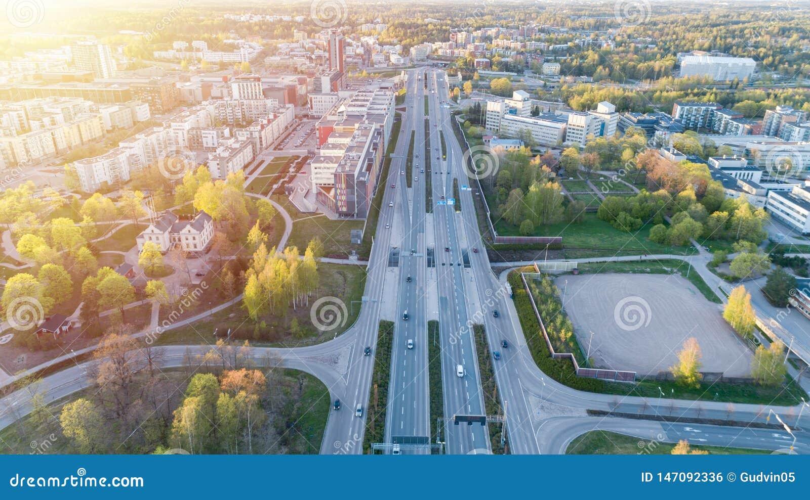 Ideia aérea de uma interseção grande da estrada em Finlandia, Helsínquia, no por do sol Conceito do transporte e das comunicações