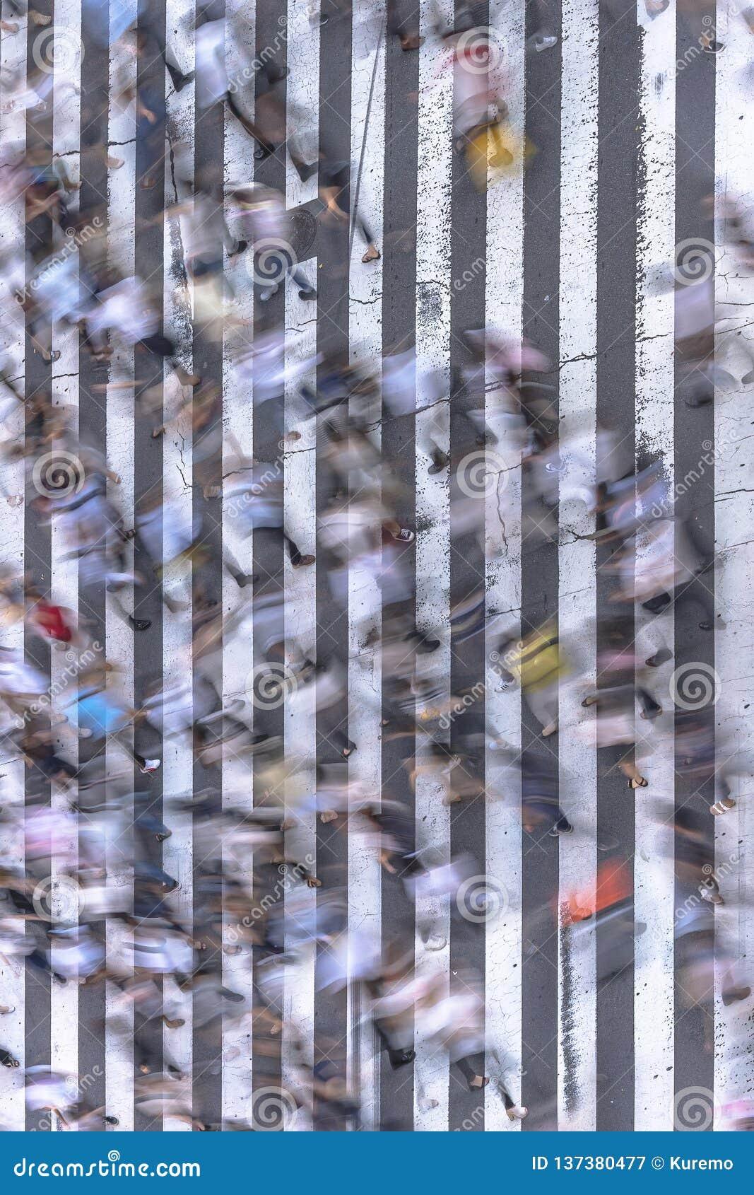 Ideia aérea de uma passagem pedestre japonesa no Tóquio pintado com as listras brancas no asfalto preto usado pelo tráfego dos ca