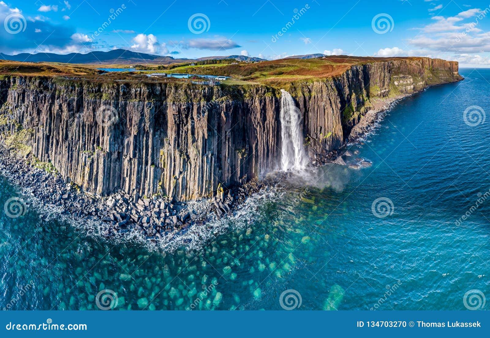 Ideia aérea do litoral dramático nos penhascos por Staffin com a cachoeira famosa da rocha do kilt - ilha de Skye -