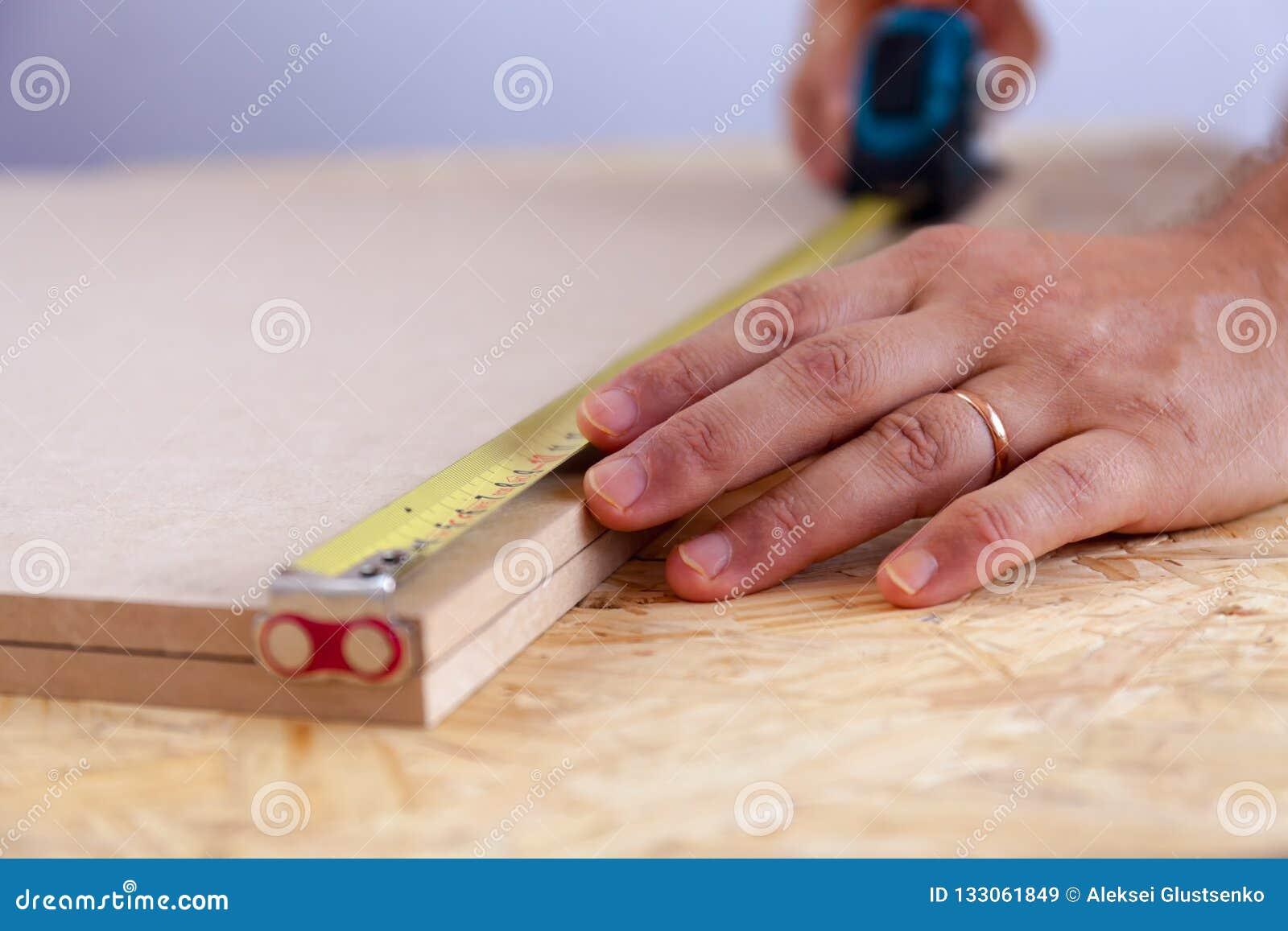 Ideia ascendente próxima das mãos de um homem que medem uma parte de madeira com uma fita handyman medida