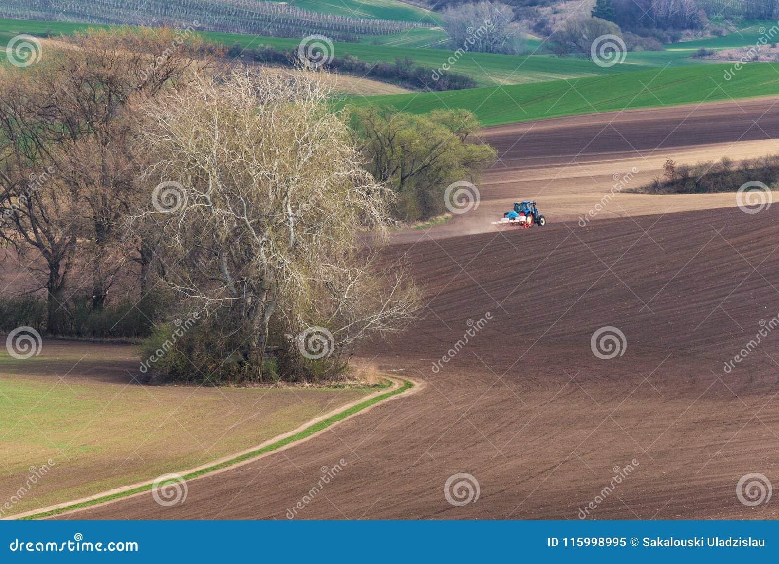Ideia cênico de cultivar BlueTractor com grade vermelha que a mola de aradura e de pulverização de Brown coloca Trator azul peque