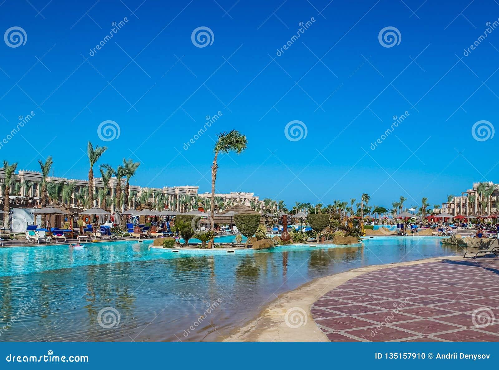 Ideia da área de recreação dos hotel's na praia e na costa de mar, palmeiras sob o céu azul de um dia ensolarado