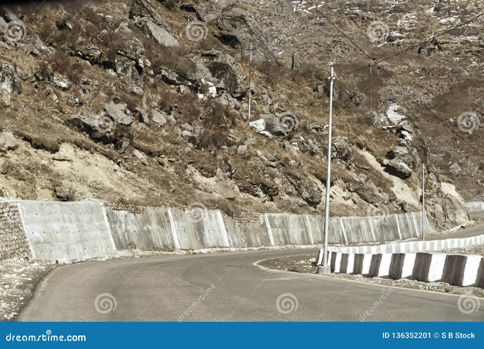 Ideia da estrada da estrada da beira de China da Índia perto da passagem de montanha do La de Nathu nos Himalayas que conecta o e