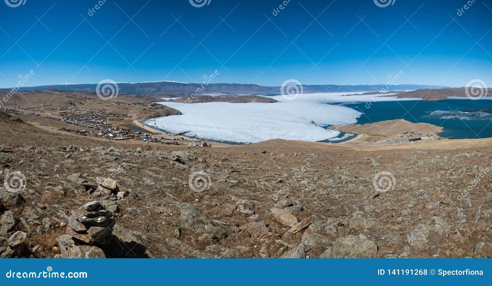 Ideia da paisagem da mola em Sibéria com parte do Lago Baikal congelado na distância da vista superior