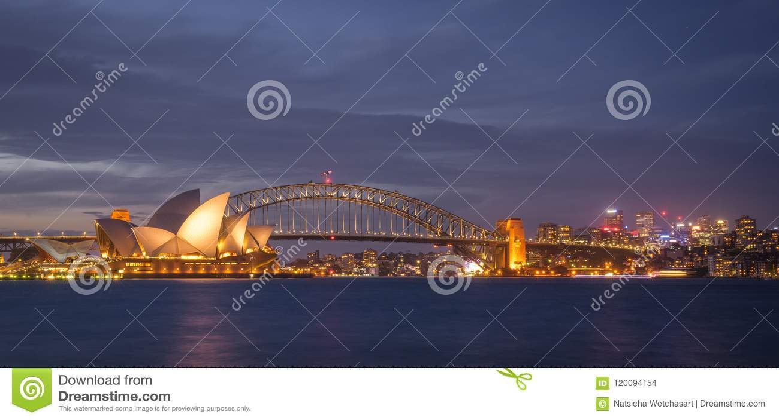 Ideia de Anoramic da arquitetura da cidade de Sydney no crepúsculo através do porto da opinião de jardim botânico