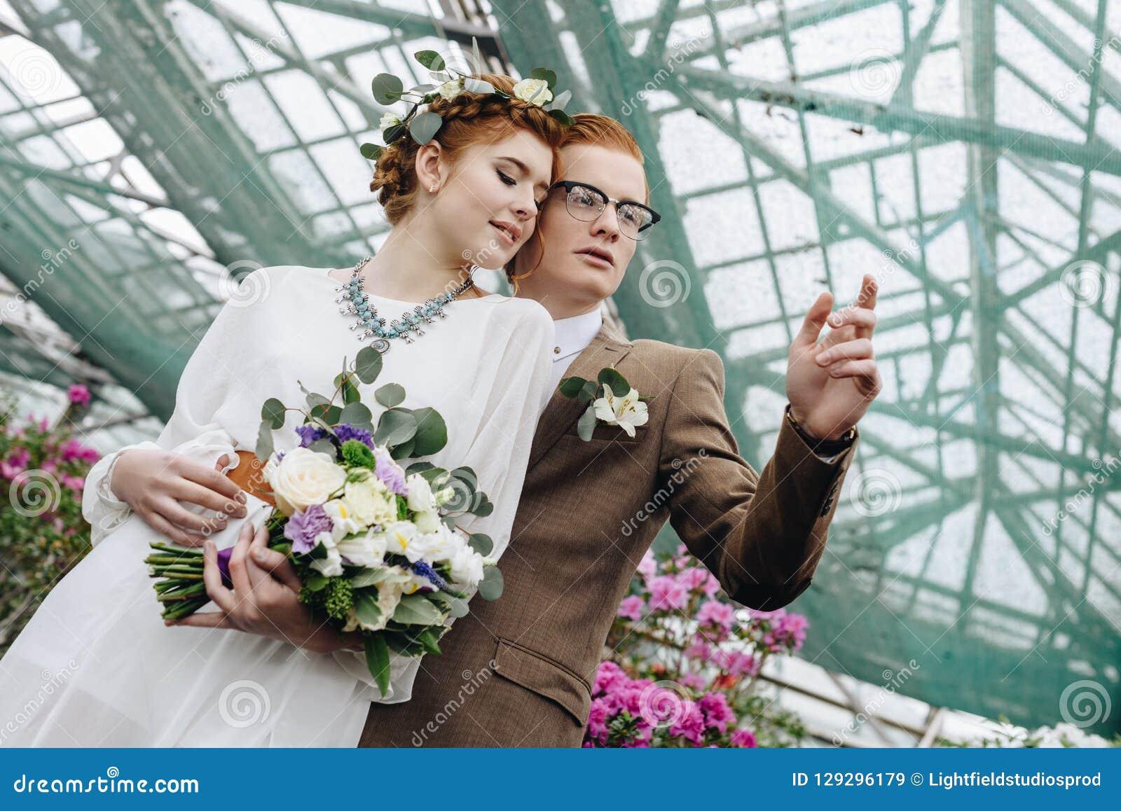 Ideia de baixo ângulo dos pares novos bonitos do casamento do ruivo que estão junto e que olham afastado