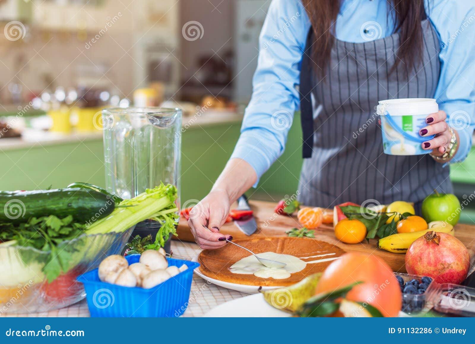 Ideia do close-up das mãos fêmeas que espalham o leite condensado na camada do bolo que está na cozinha
