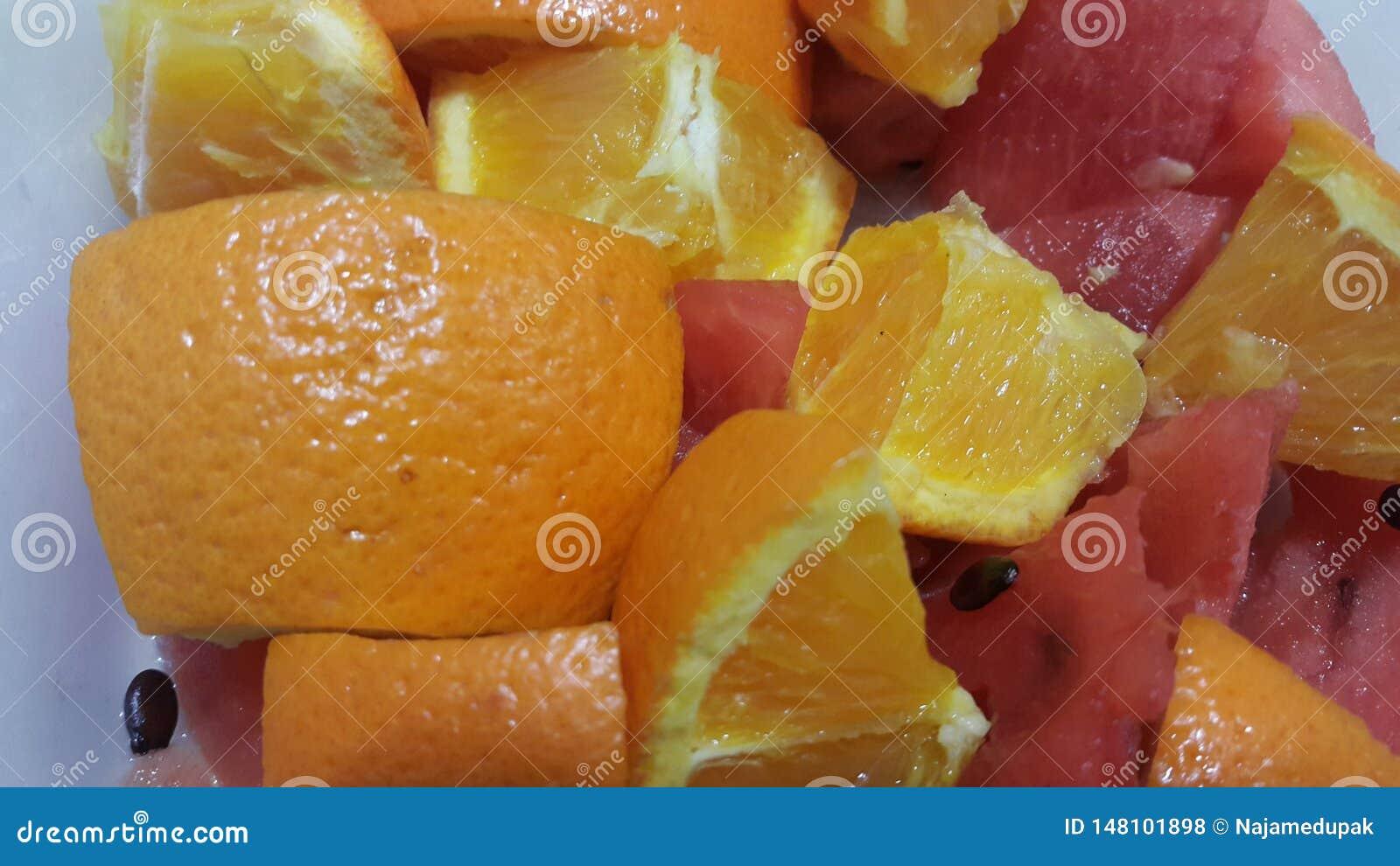 Ideia do close up de fatias misturadas dos frutos de laranjas do citrino e de melancia vermelha doce