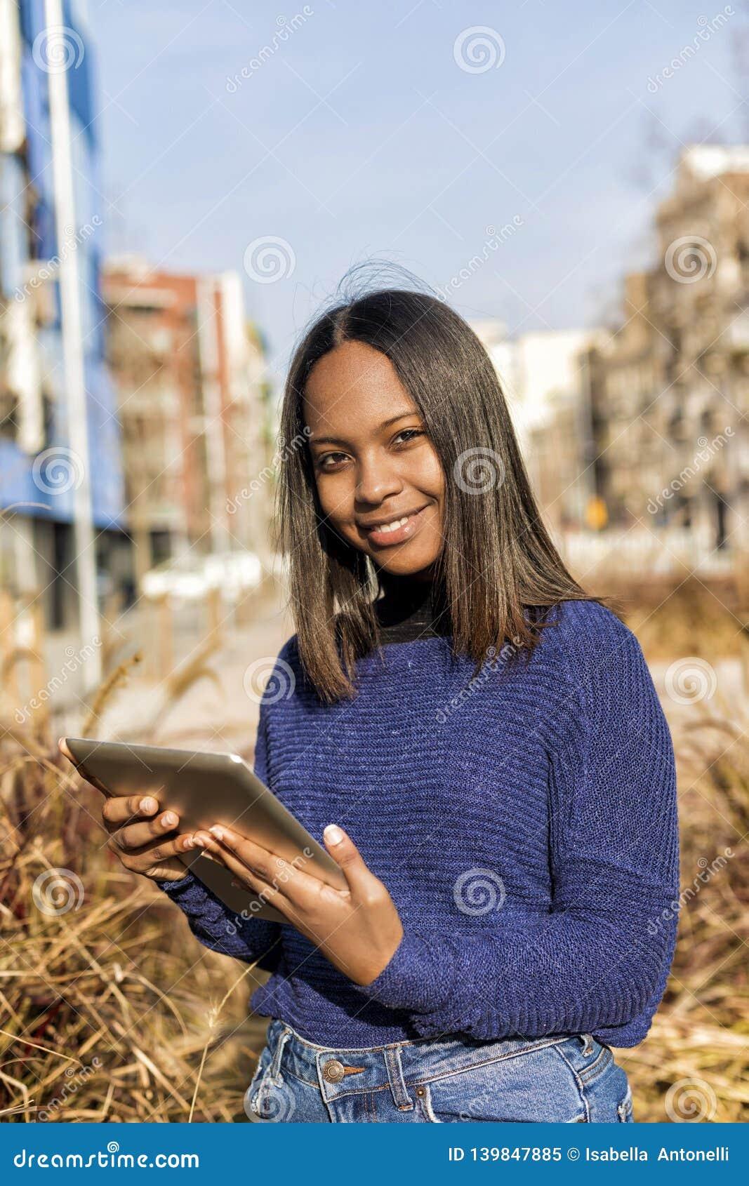 Ideia lateral de uma posição afro-americano da menina, ao guardar a tabuleta em suas mãos e ao olhar a câmera