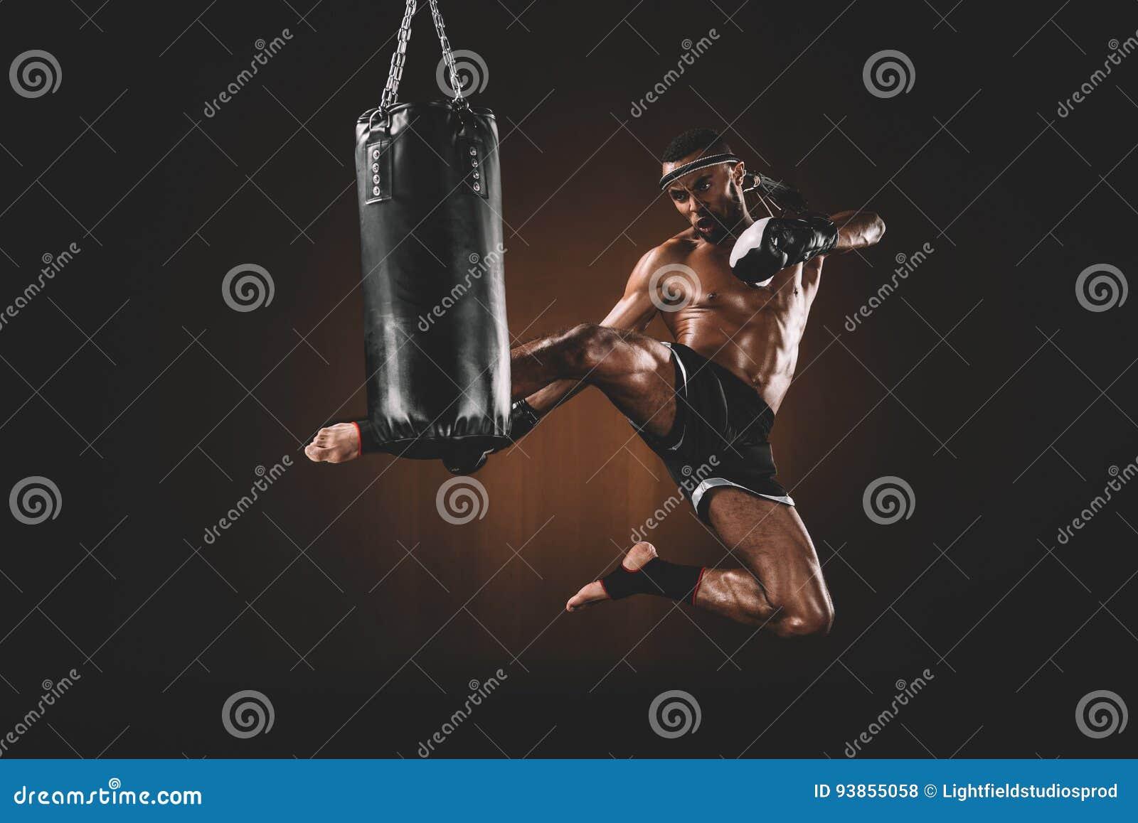 Ideia lateral do pontapé praticando tailandês muay focalizado do lutador no saco de perfuração