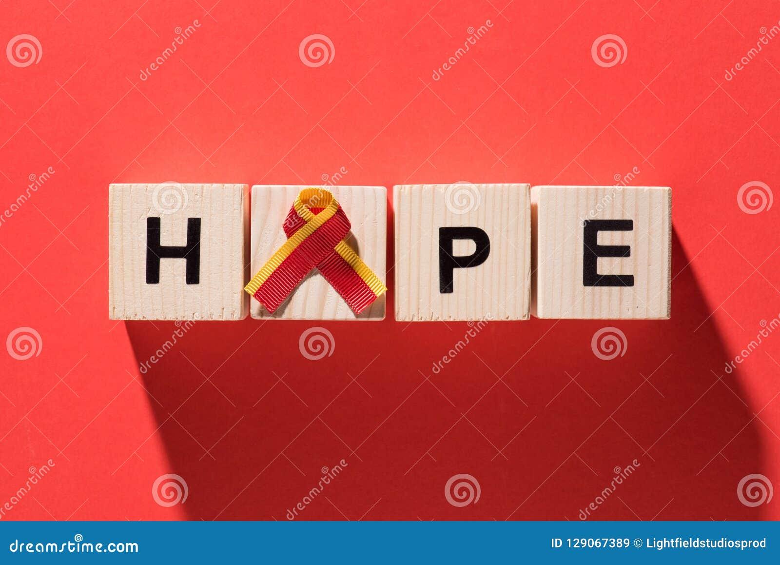 Ideia superior da fita e da esperança da rotulação dos cubos de madeira na hepatite vermelha do mundo do fundo