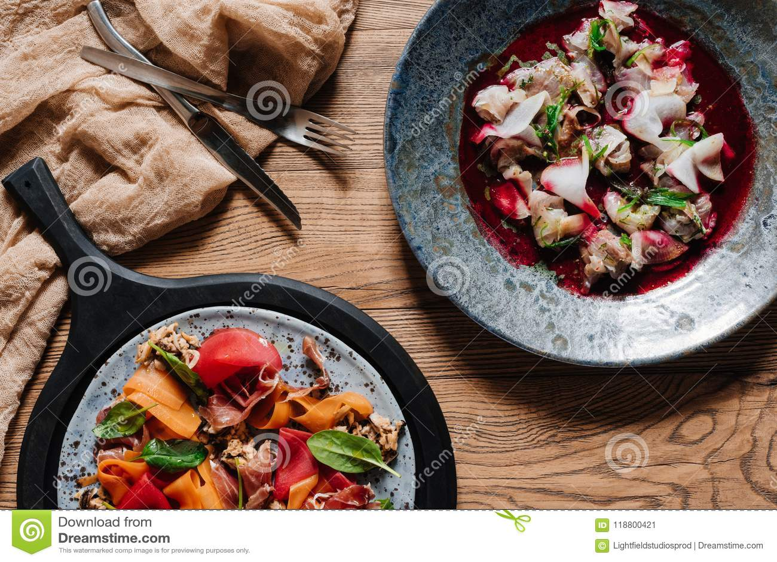Ideia superior da salada gourmet com mexilhões e do ceviche delicioso com o dorado na tabela de madeira