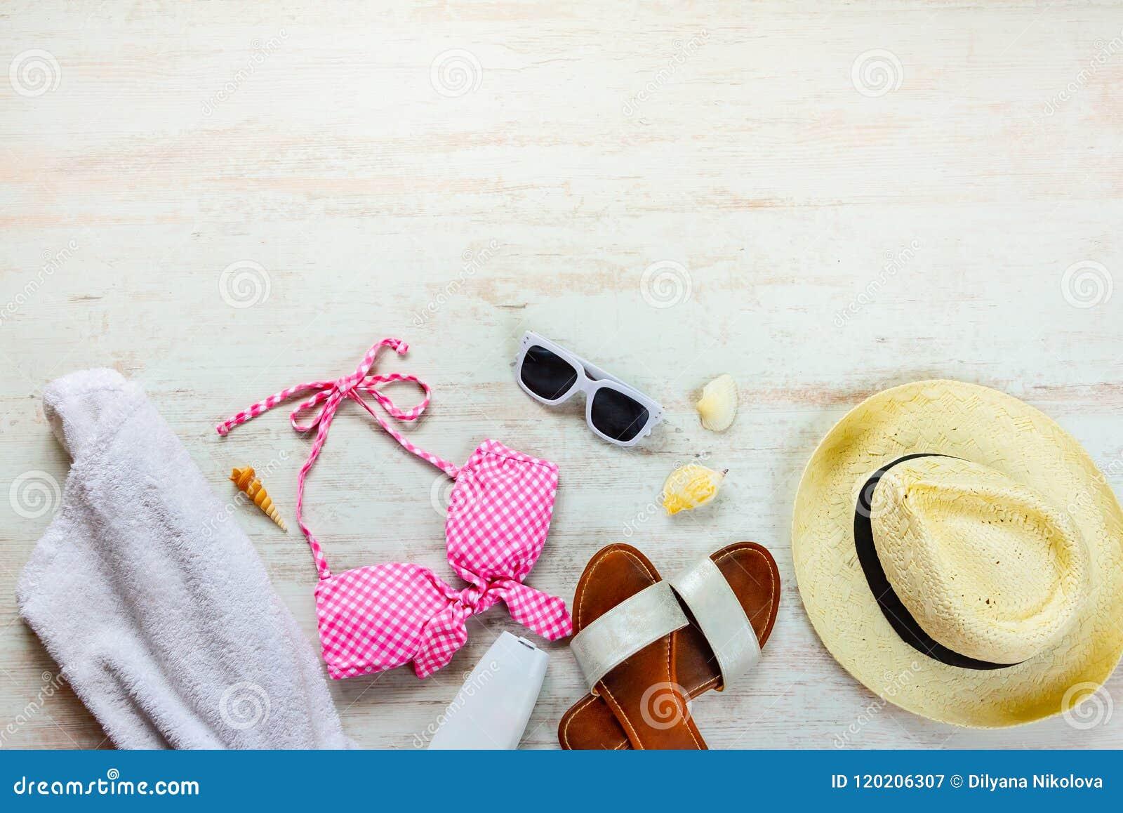 Ideia superior de duas accessoties cor-de-rosa partes do terno e da praia de natação sobre o fundo de madeira Copie o space=