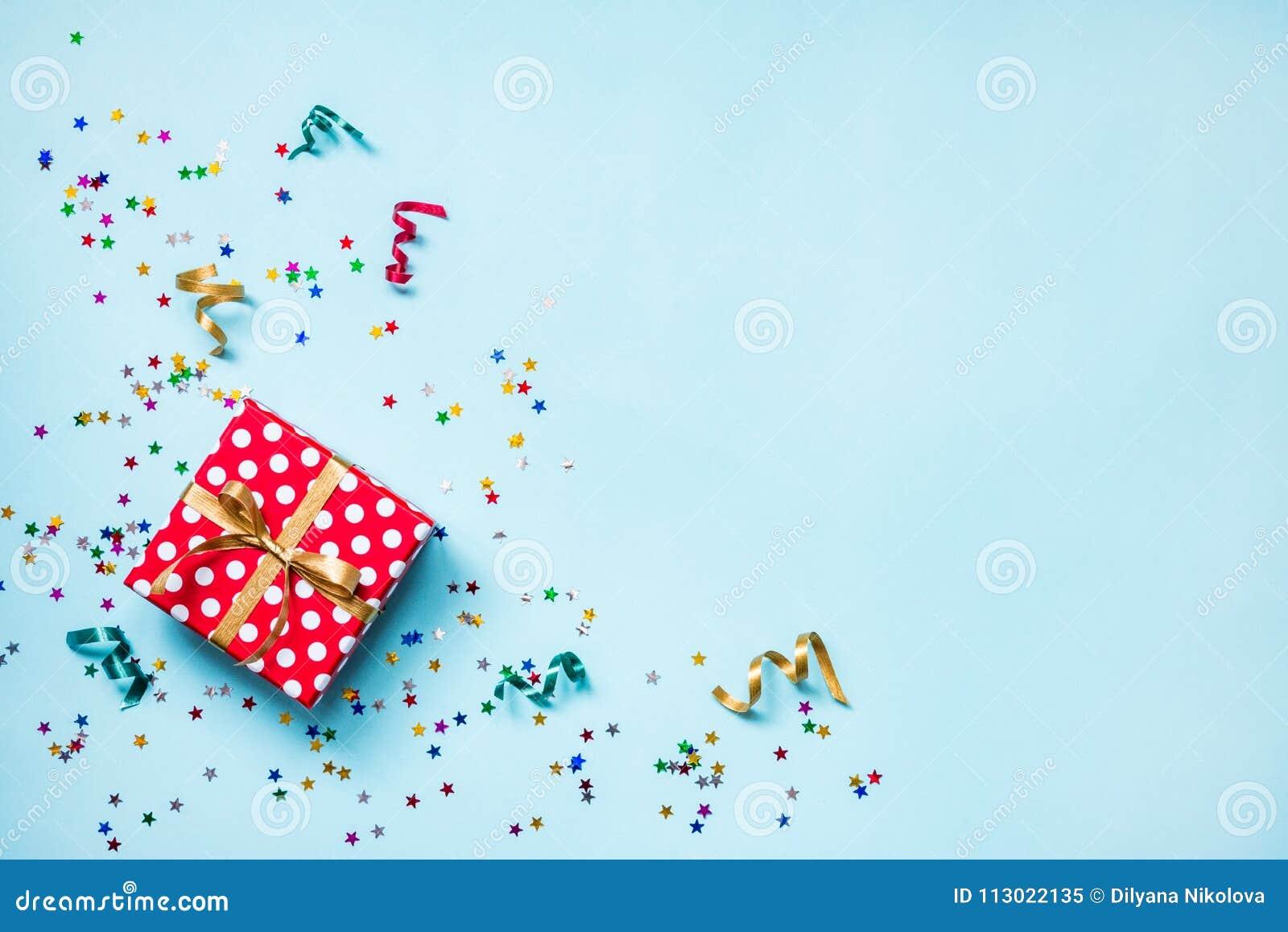 A ideia superior de um vermelho pontilhou a caixa de presente, confetes dados forma estrela de brilho dispersados e fitas colorid