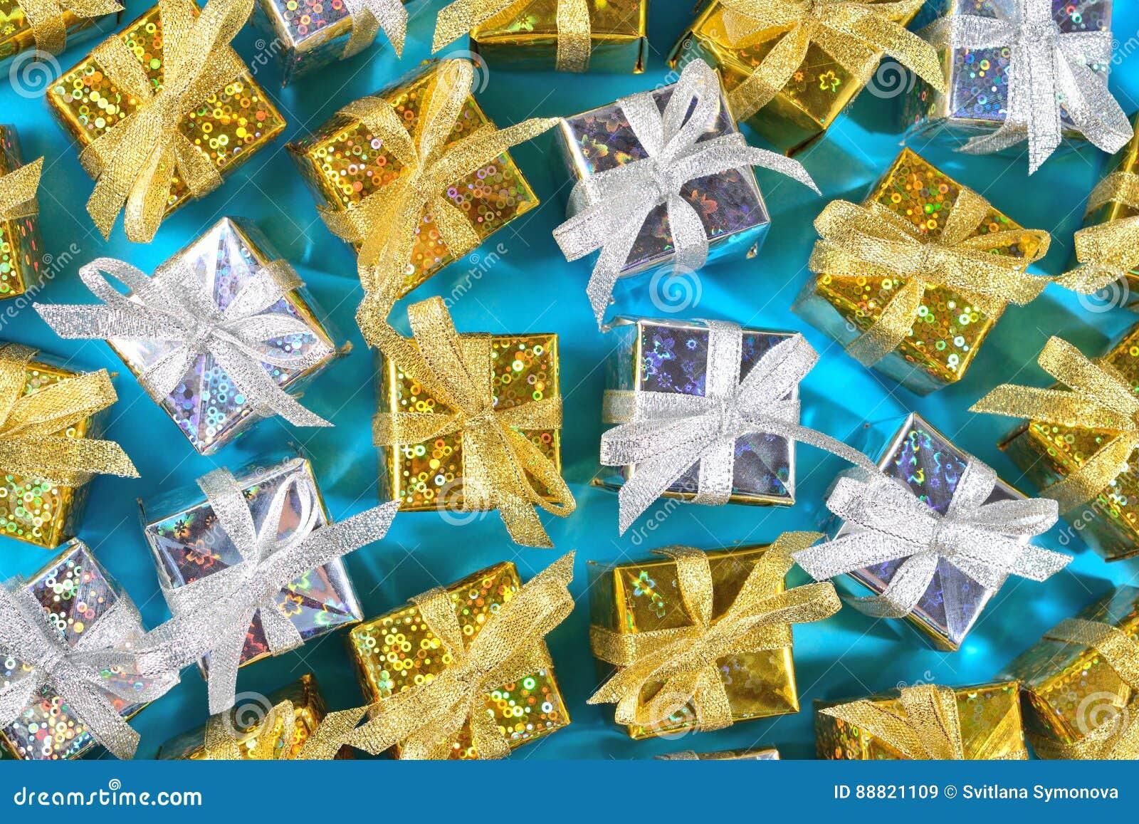 Ideia superior do close-up dourado e de prata dos presentes em um azul