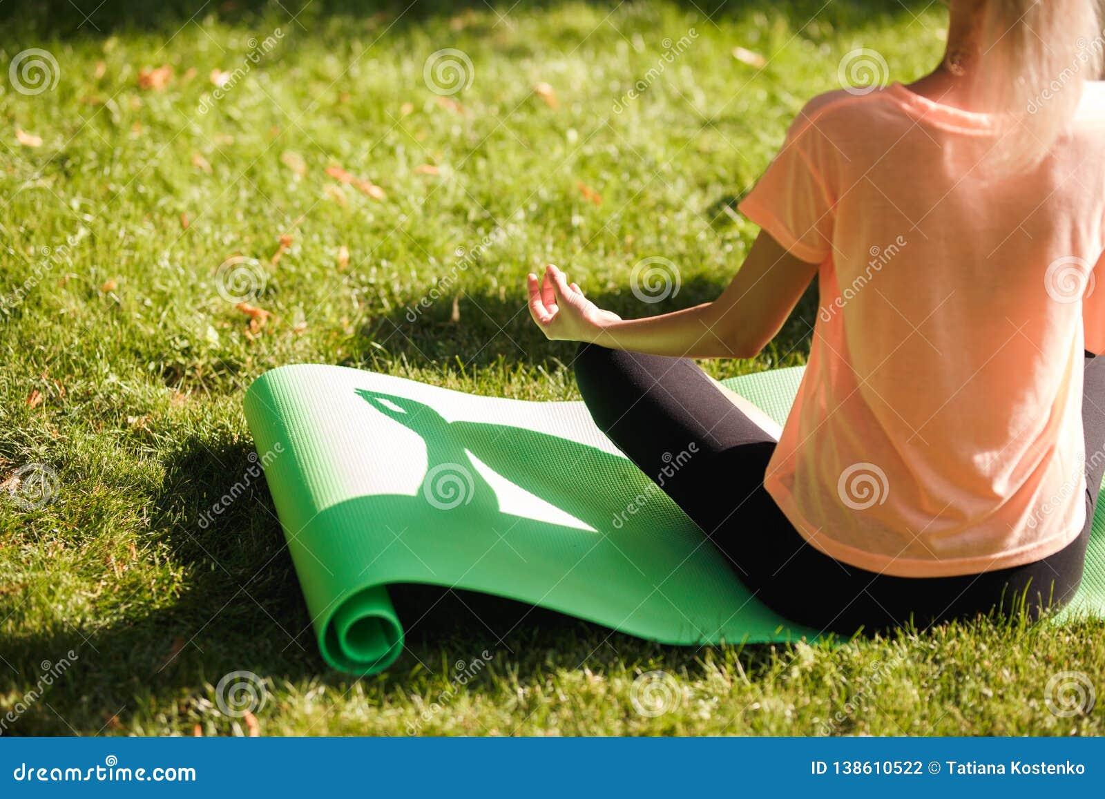A ideia traseira da ioga praticando da mulher senta-se na posição de lótus Conceito saudável do estilo de vida