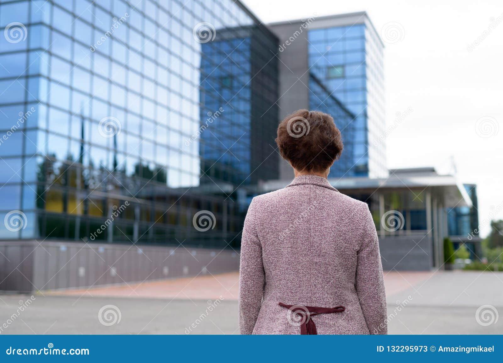 Ideia traseira da opinião madura de Looking At The da mulher de negócios da cidade