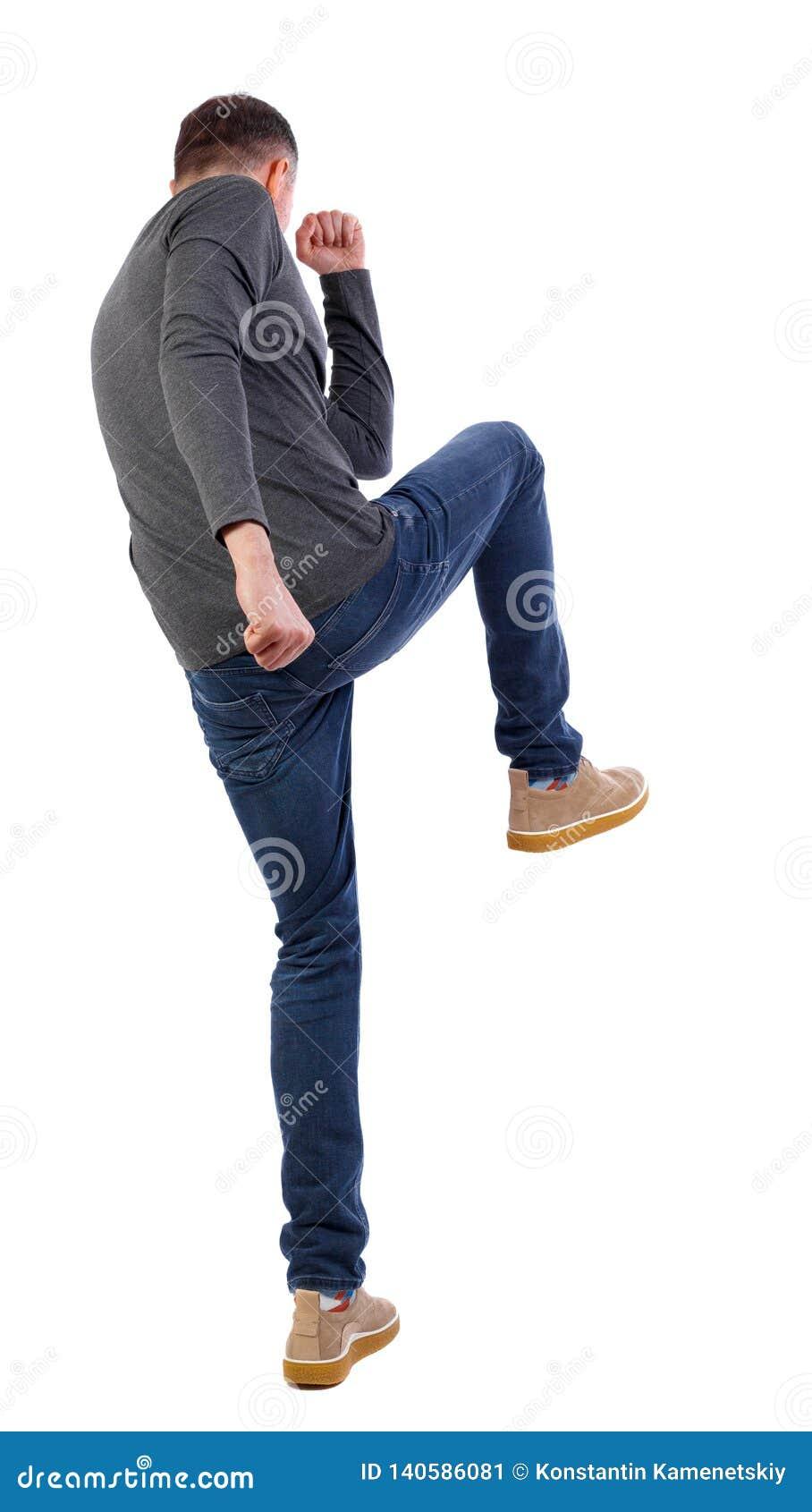 Ideia traseira das lutas engraçadas do indivíduo magro que acenam seus braços e pés