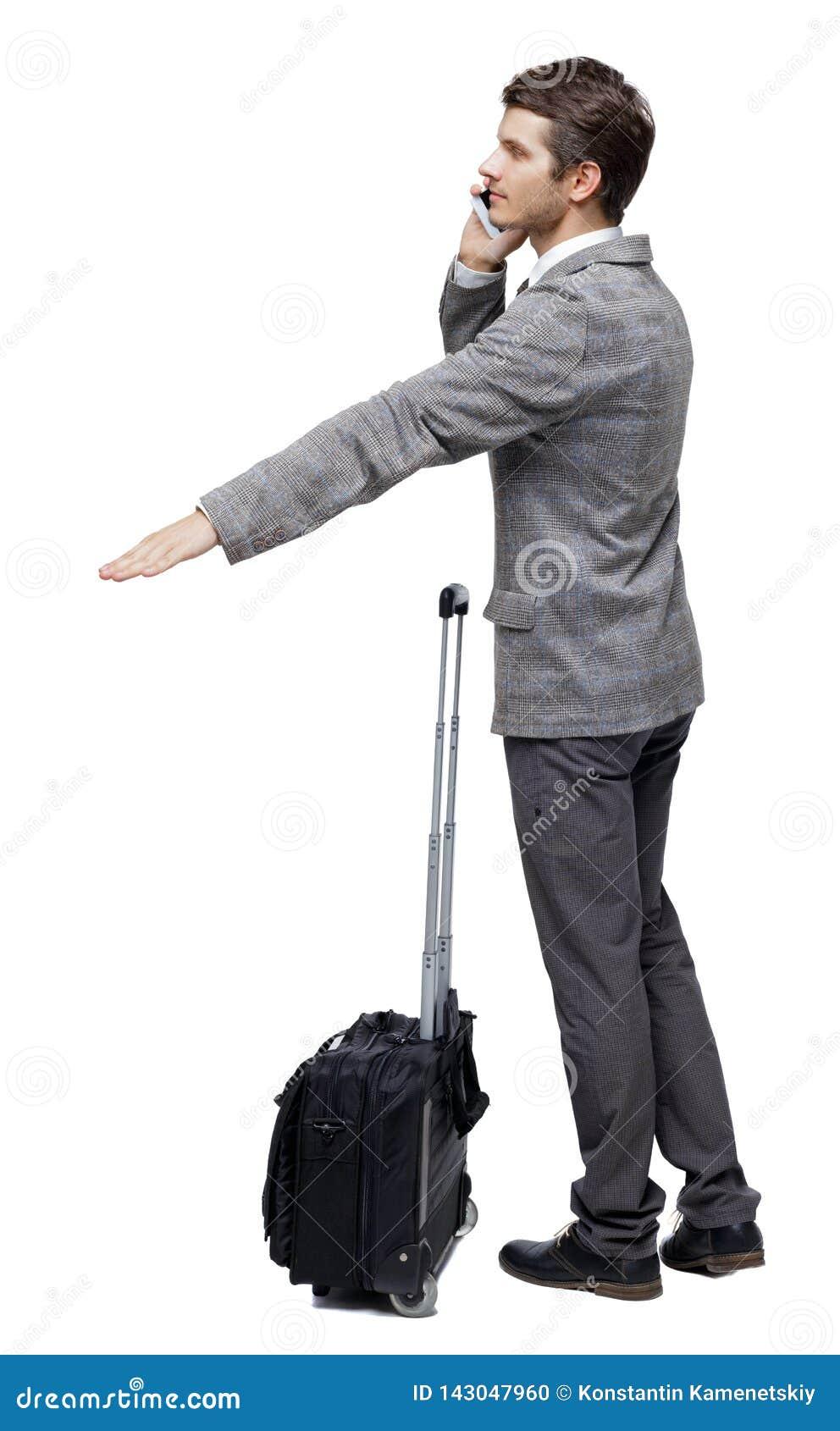 Ideia traseira de apontar o homem de negócio com mala de viagem que fala no telefone