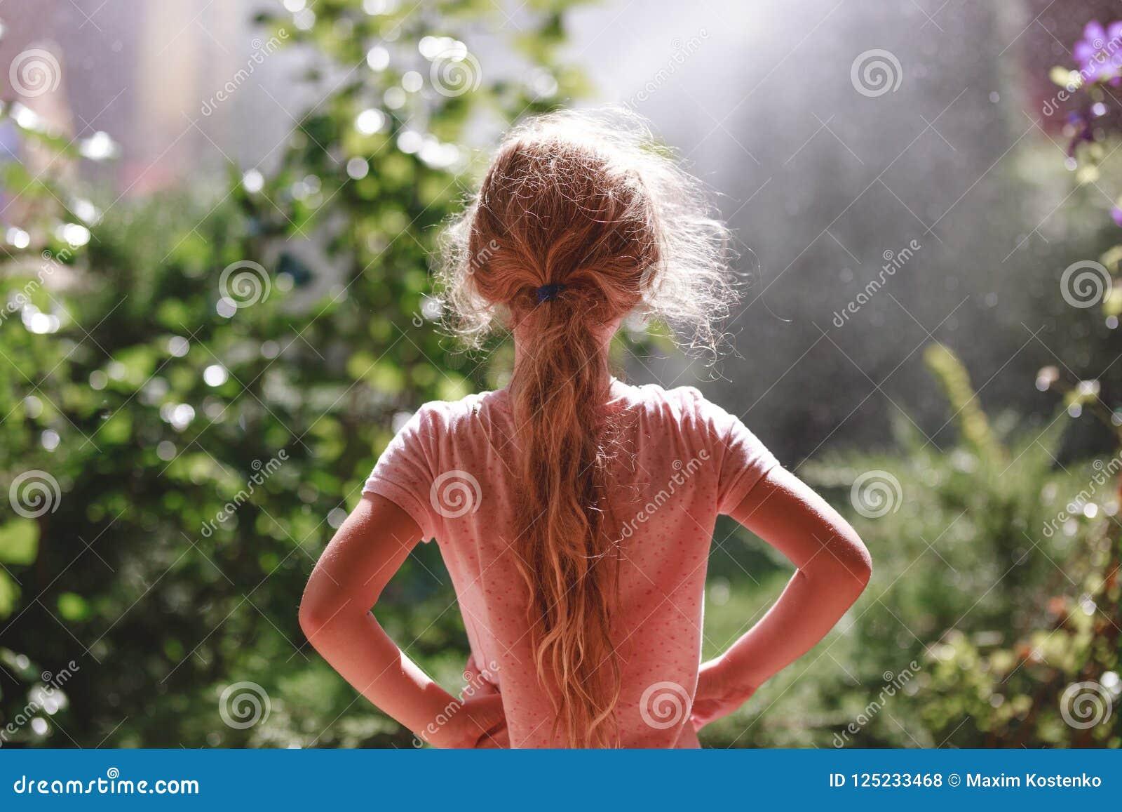 Ideia traseira de sete anos de pyjamas vestindo da menina loura idosa que estão exteriores no jardim home no amanhecer