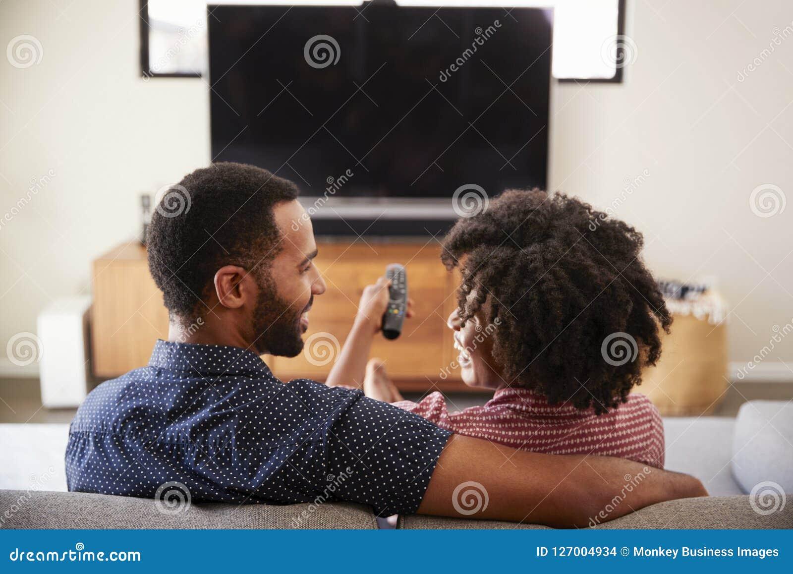 Ideia traseira dos pares que sentam-se na tevê de Sofa Watching junto