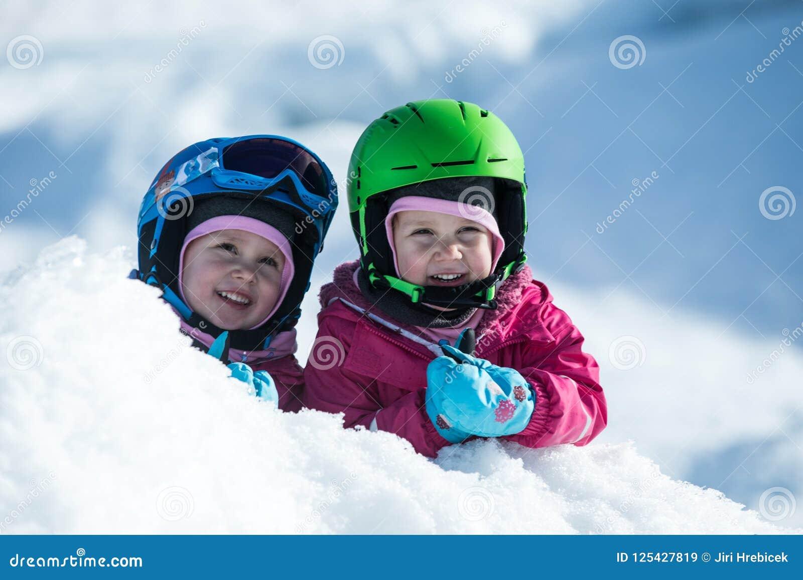 Identiskt kopplar samman har gyckel i snö Ungar med säkerhetshjälmen Vintersport för familj Små ungar utanför, schweiziska fjällä