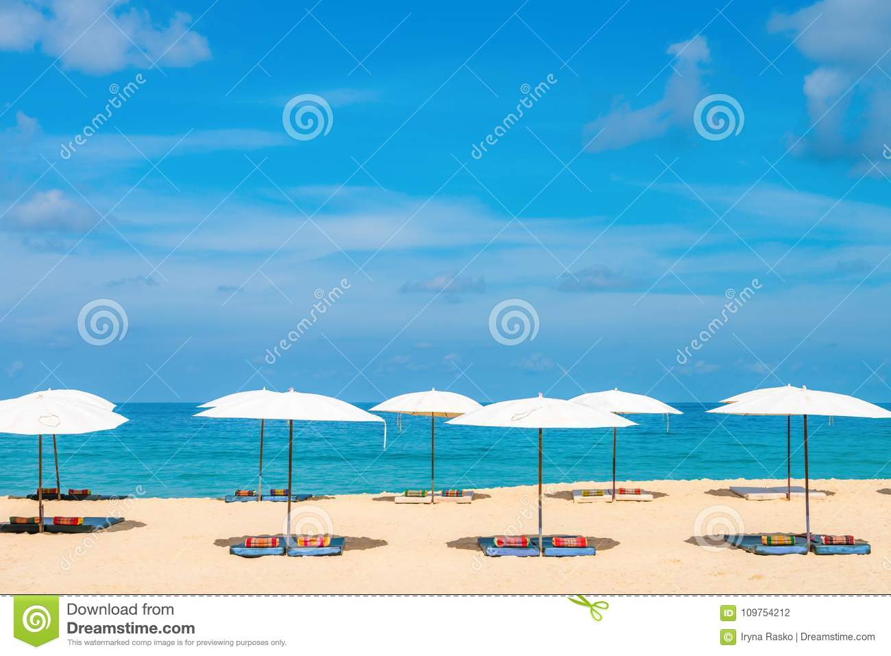 Idollic beach relaxing concept with white parasols on sand