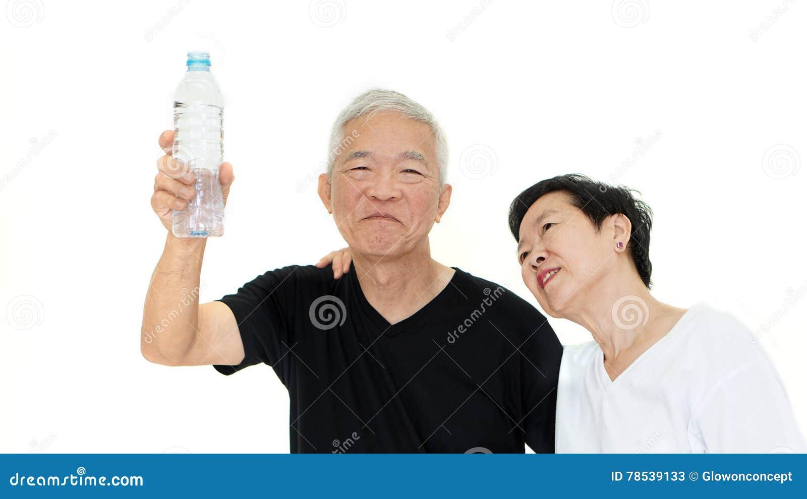 Idrato senior asiatico di soggiorno della bottiglia di acqua della tenuta delle coppie per salute