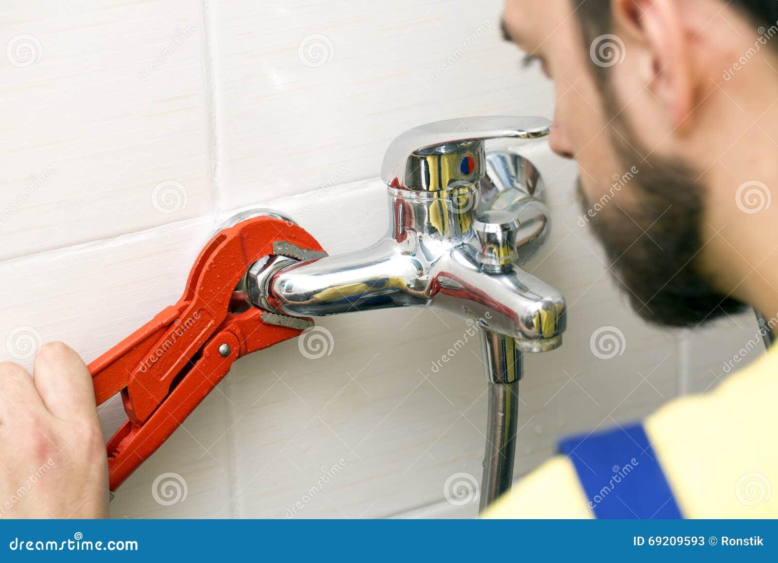 Idraulico che installa il rubinetto di acqua nel bagno