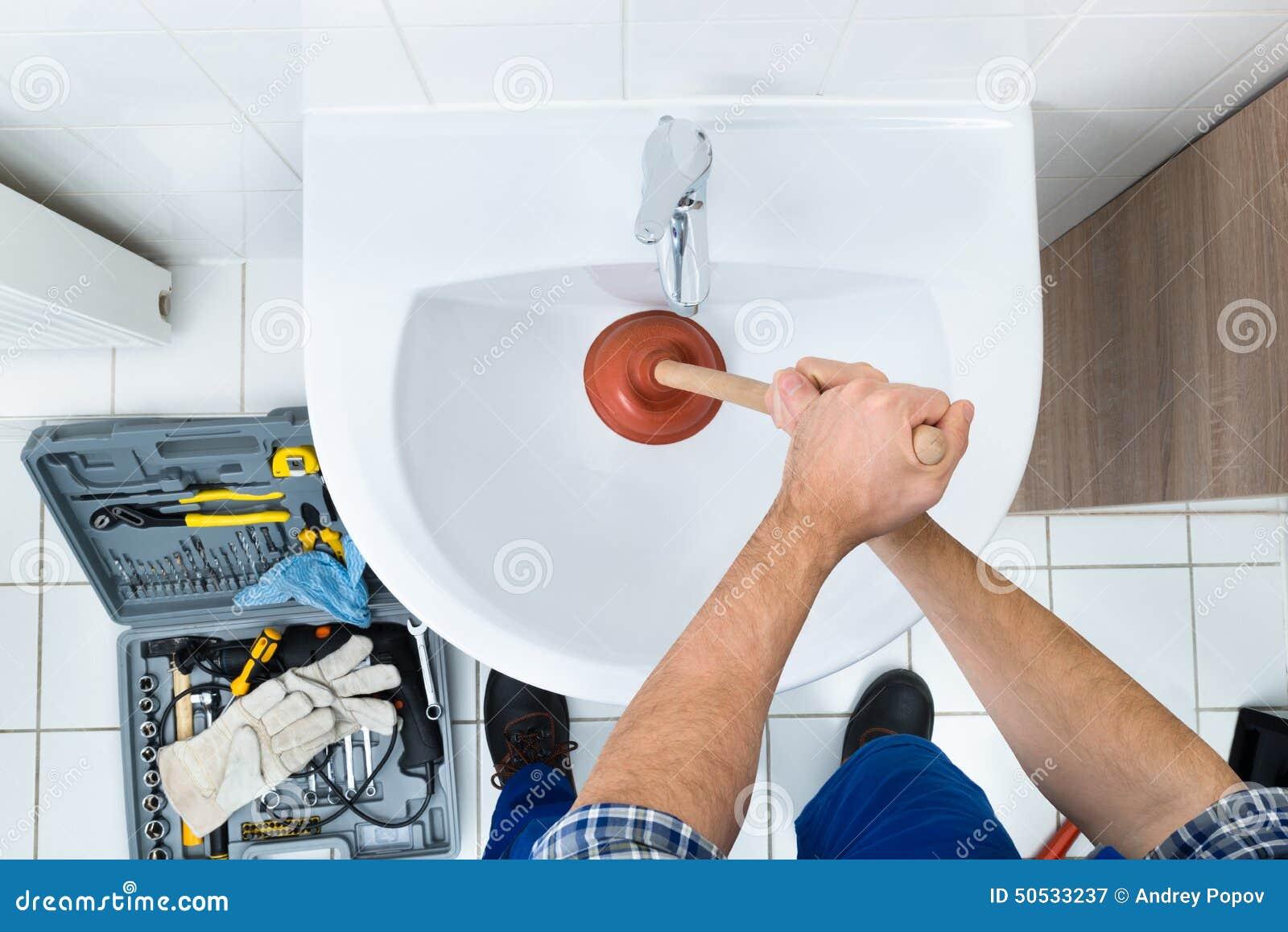 Idraulico maschio che utilizza tuffatore nel lavandino del bagno