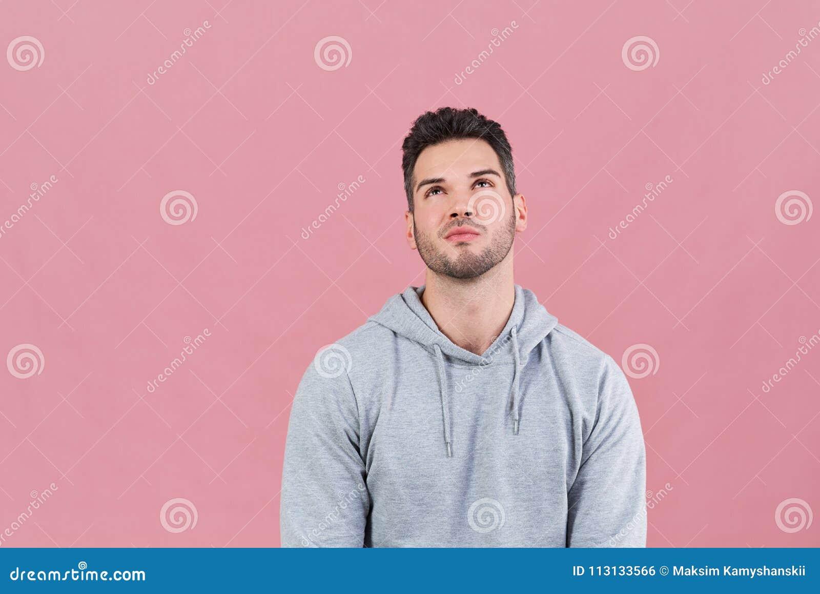 Idrotts- attraktiv man i en hoodie som ser upp med längtande minnas uttryck Begrepp av valet, beslut, minnen