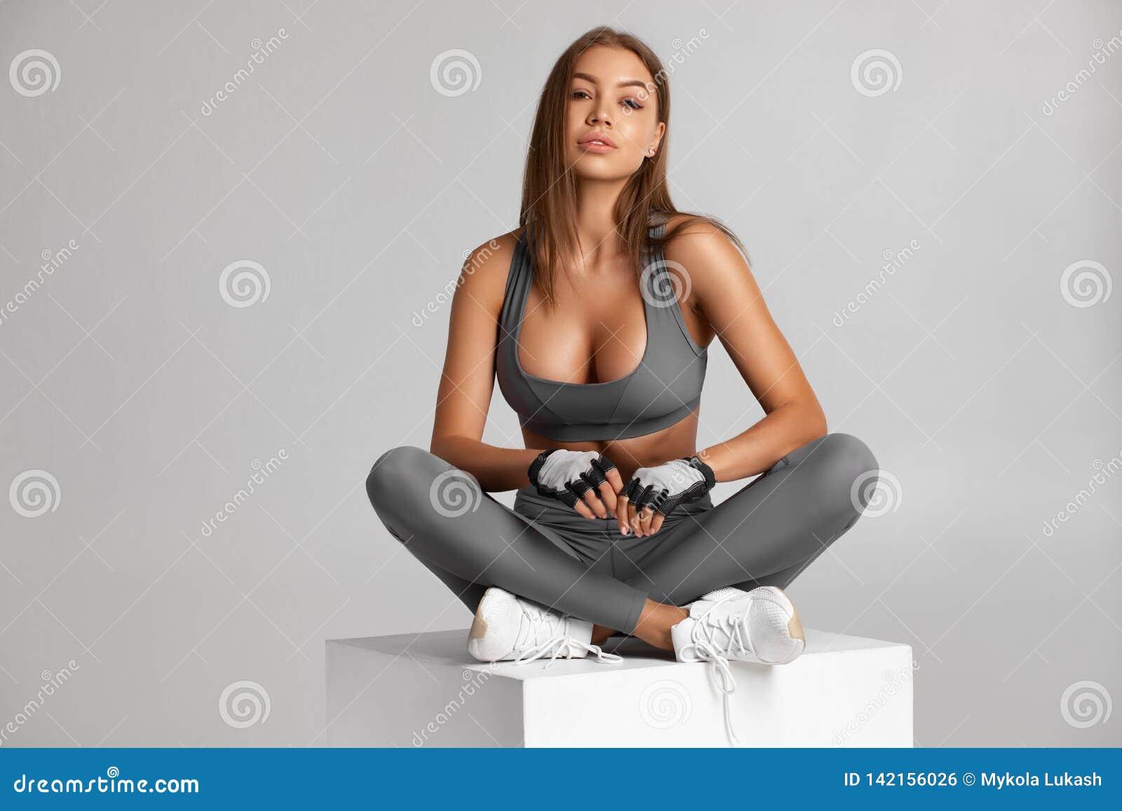 Idrotts- flickasammanträde Härlig konditionkvinna som isoleras på grå färgerna