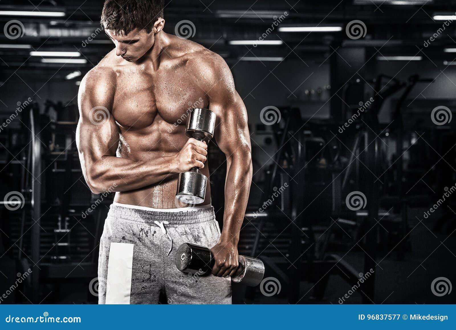 Idrotts- shirtless ung sportman - konditionmodellen rymmer hanteln i idrottshall Kopieringsutrymmeför din text