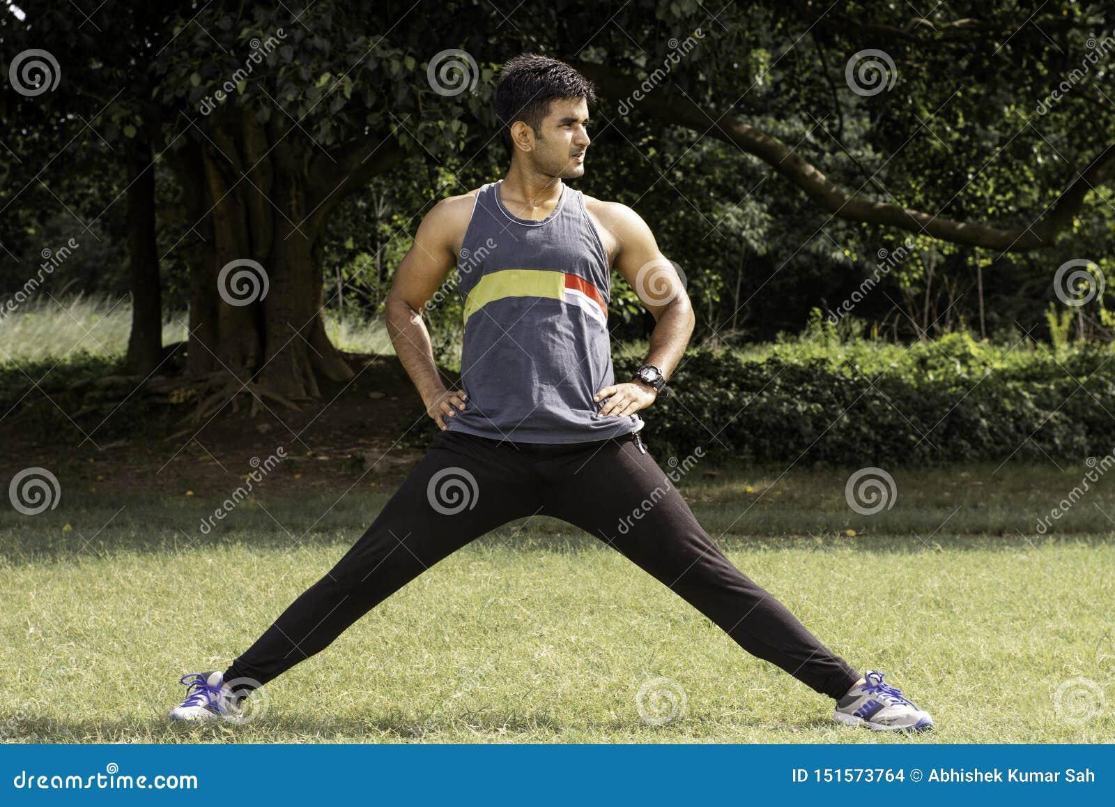 Idrotts- ung man som streching hans ben i sportjordningen Sunt livsstil-, kondition- och sportbegrepp