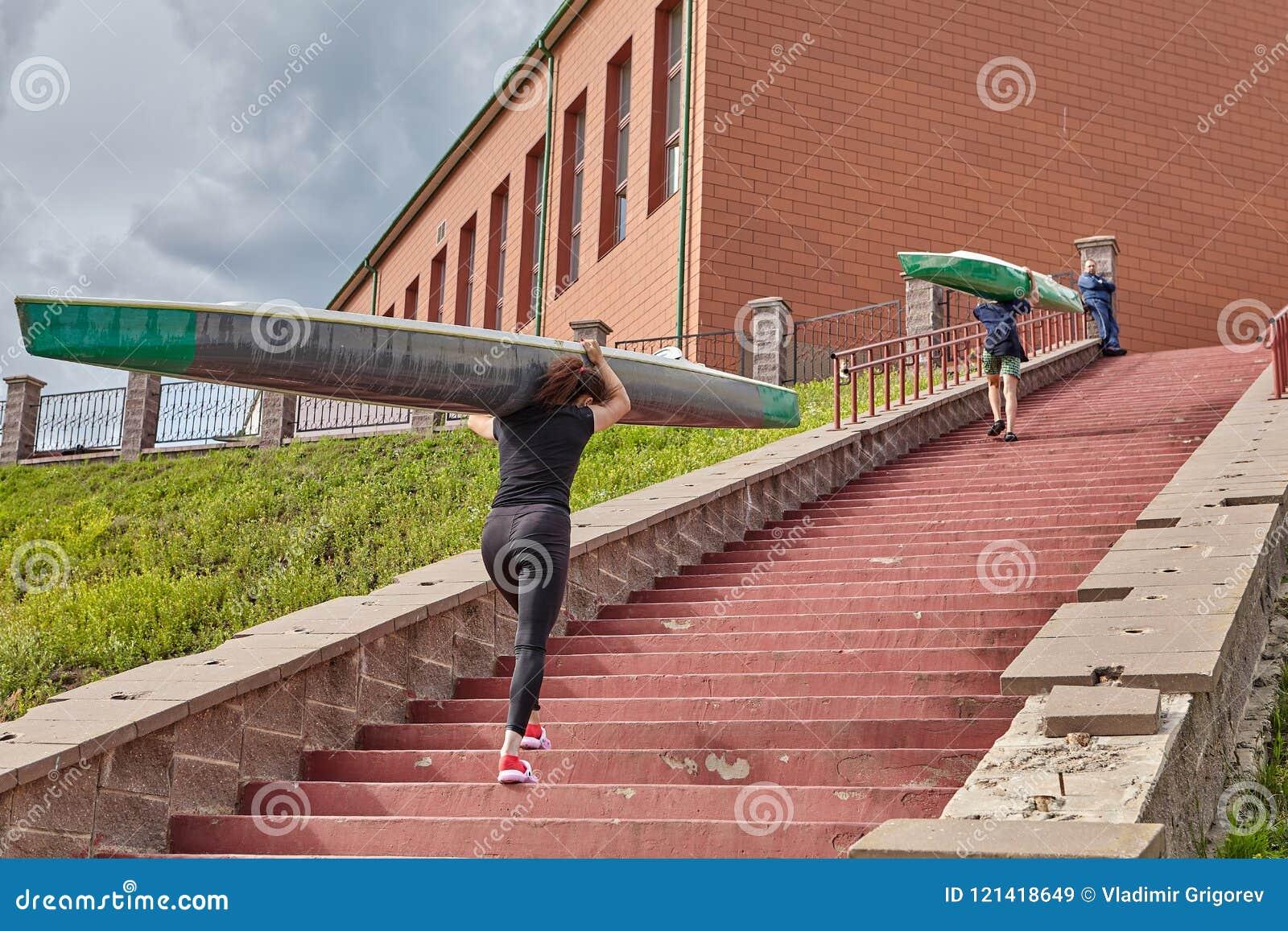Idrottsman nen går uppför trappan med kajaker på skuldror, når de har rott tra