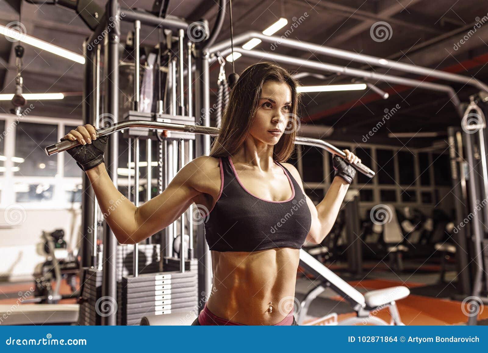 Idrottsman nenflicka i sportswear som utarbetar och utbildar henne armar och skuldror med övningsmaskinen i idrottshall