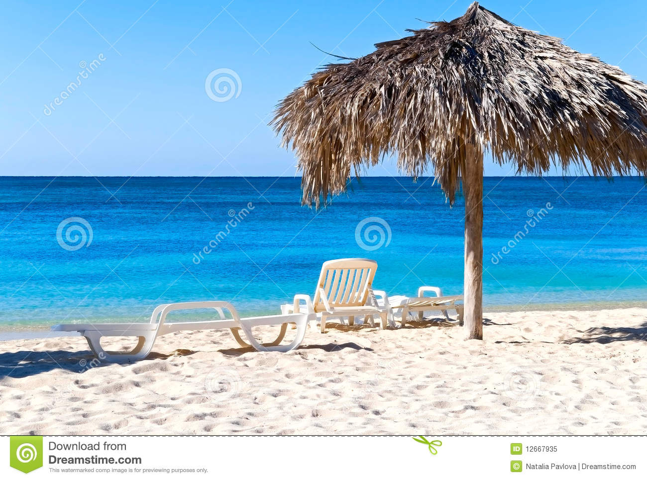 The idyllic beach with deck chairs and umbrella, Ancon, Cuba.