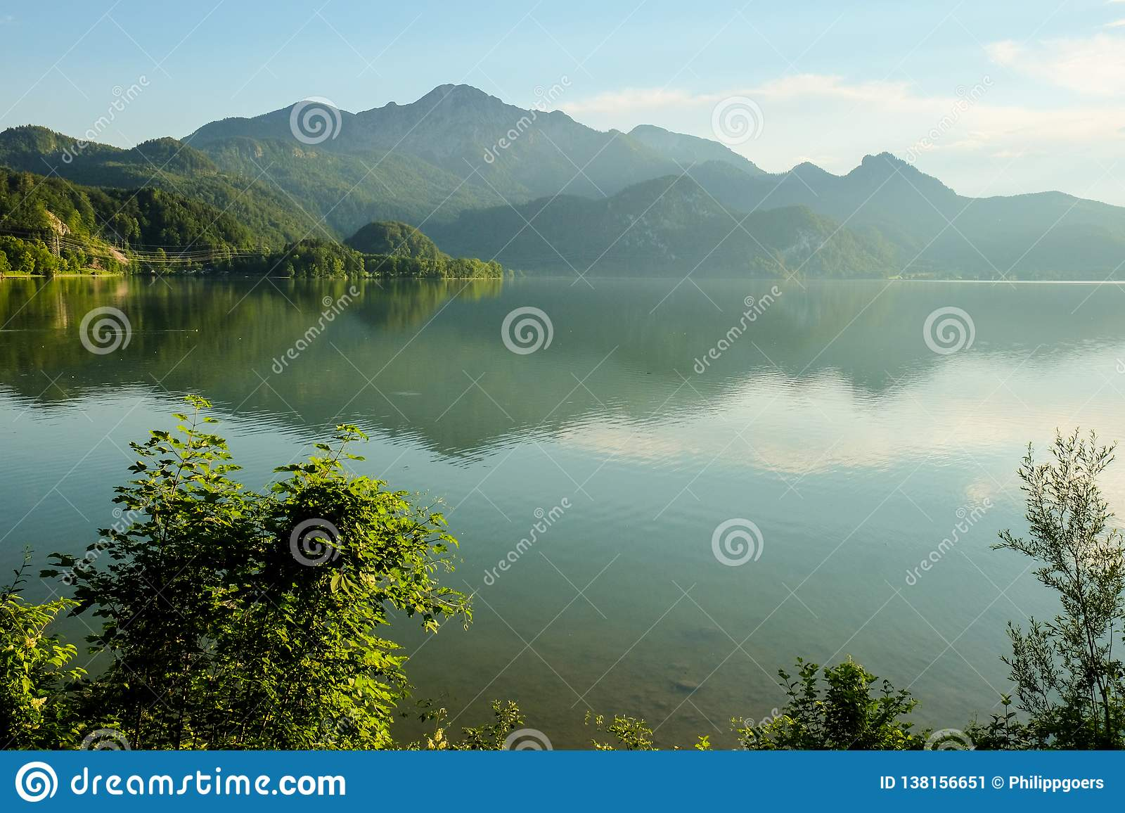 Idyllic foggy mountain landscape with a lake and mountains in the background