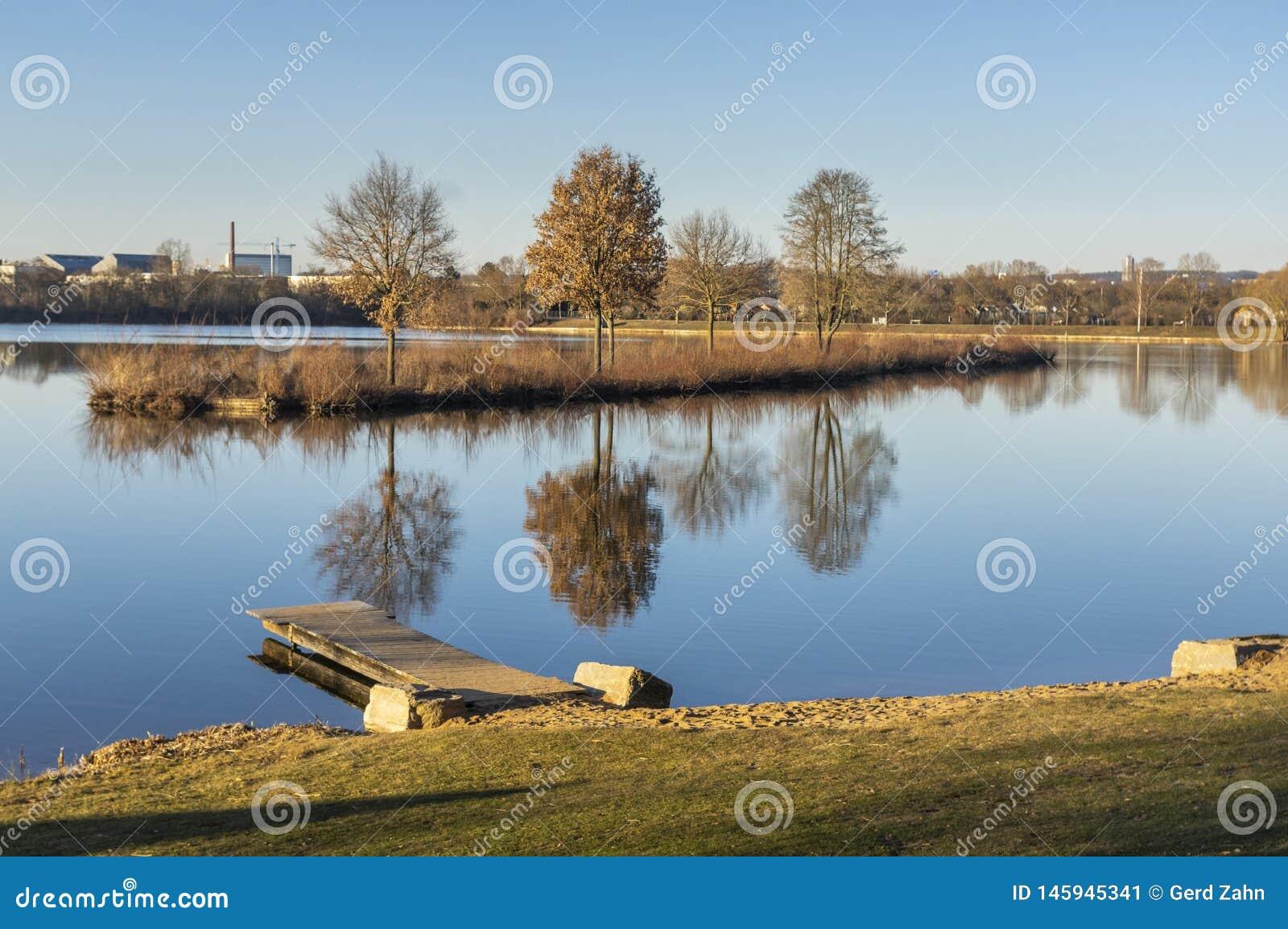 Idyllisch meer met vrije tijdsfaciliteiten en recreatief gebied in de lente met aangrenzende toewijzingen