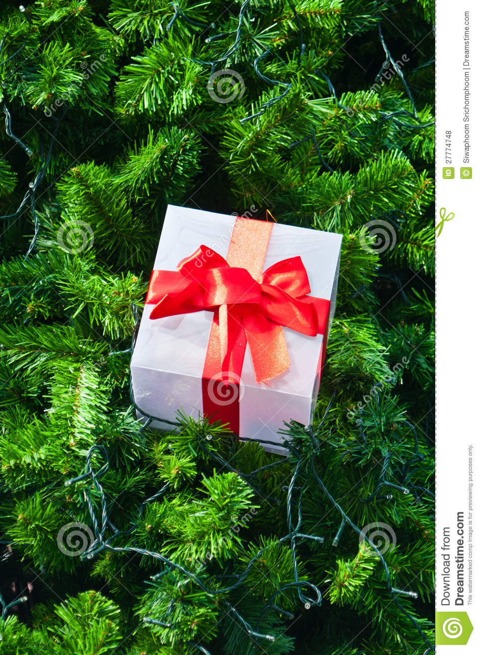 Ift box and red ribbon on christmas tree royalty free for Red ribbon around tree