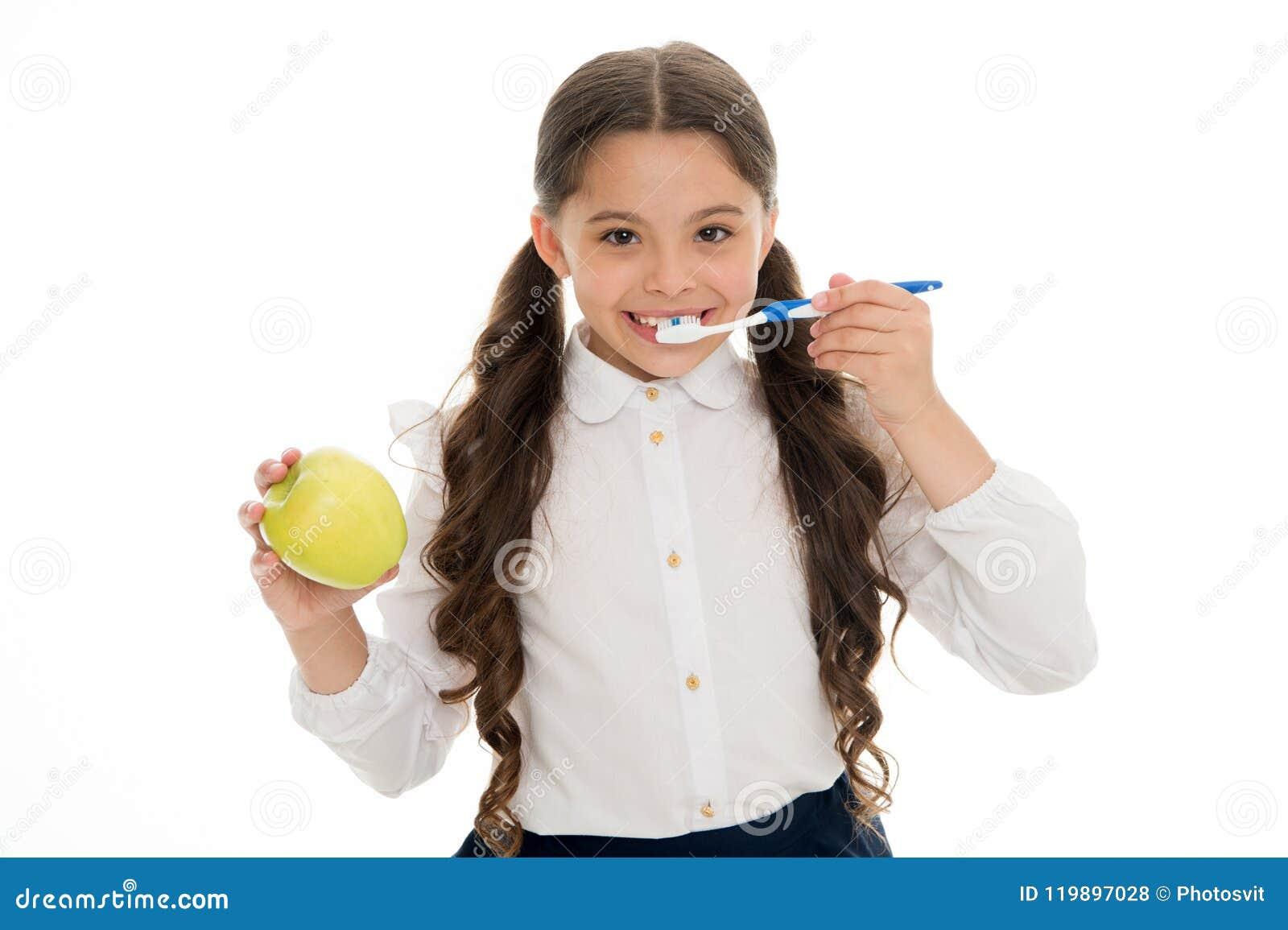 Igiene orale Spazzolino da denti delle tenute della ragazza e fondo svegli di bianco della mela La ragazza del bambino tiene il d