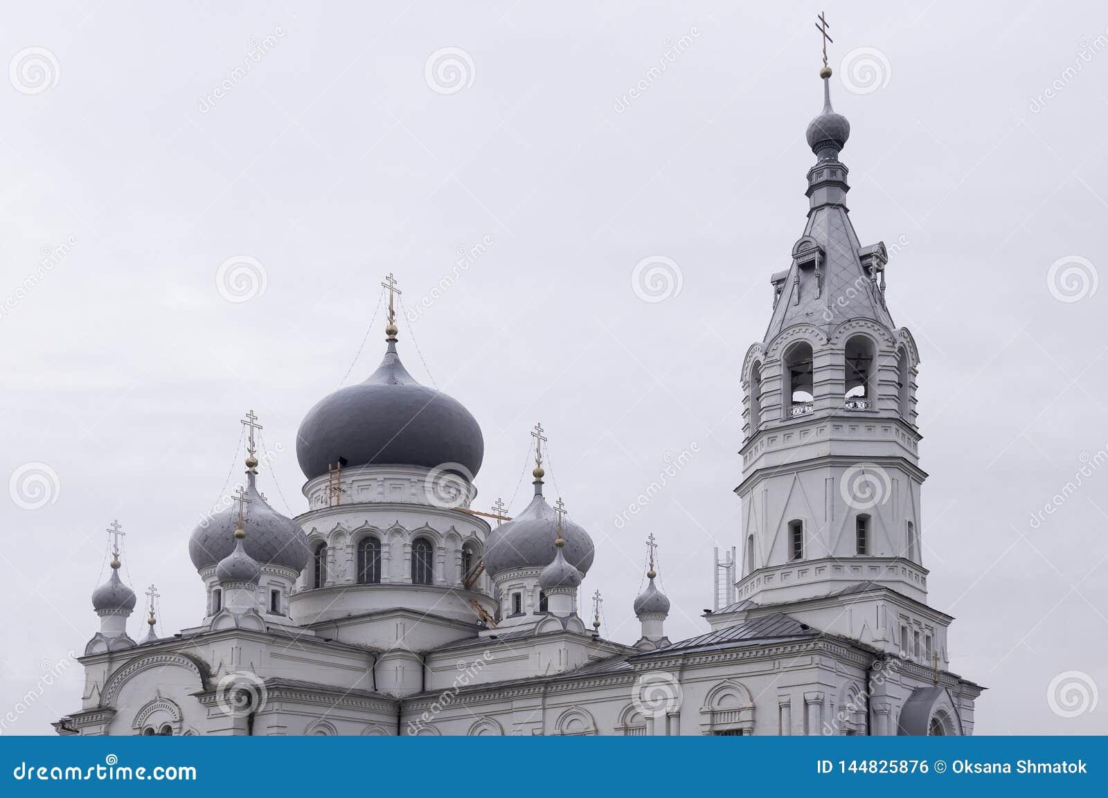 Iglesia blanca ortodoxa cristiana con las bóvedas de plata y grises con las cruces del oro Cielo gris tranquilo arriba