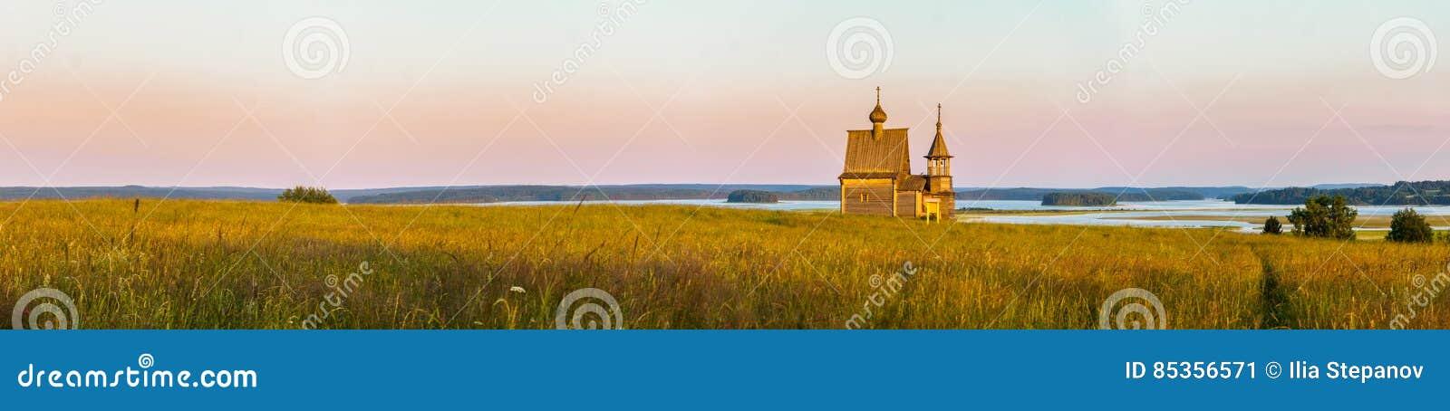 Iglesia de madera en el top de la colina Opinión de la puesta del sol del pueblo de Vershinino Región de Arkhangelsk, Rusia septe