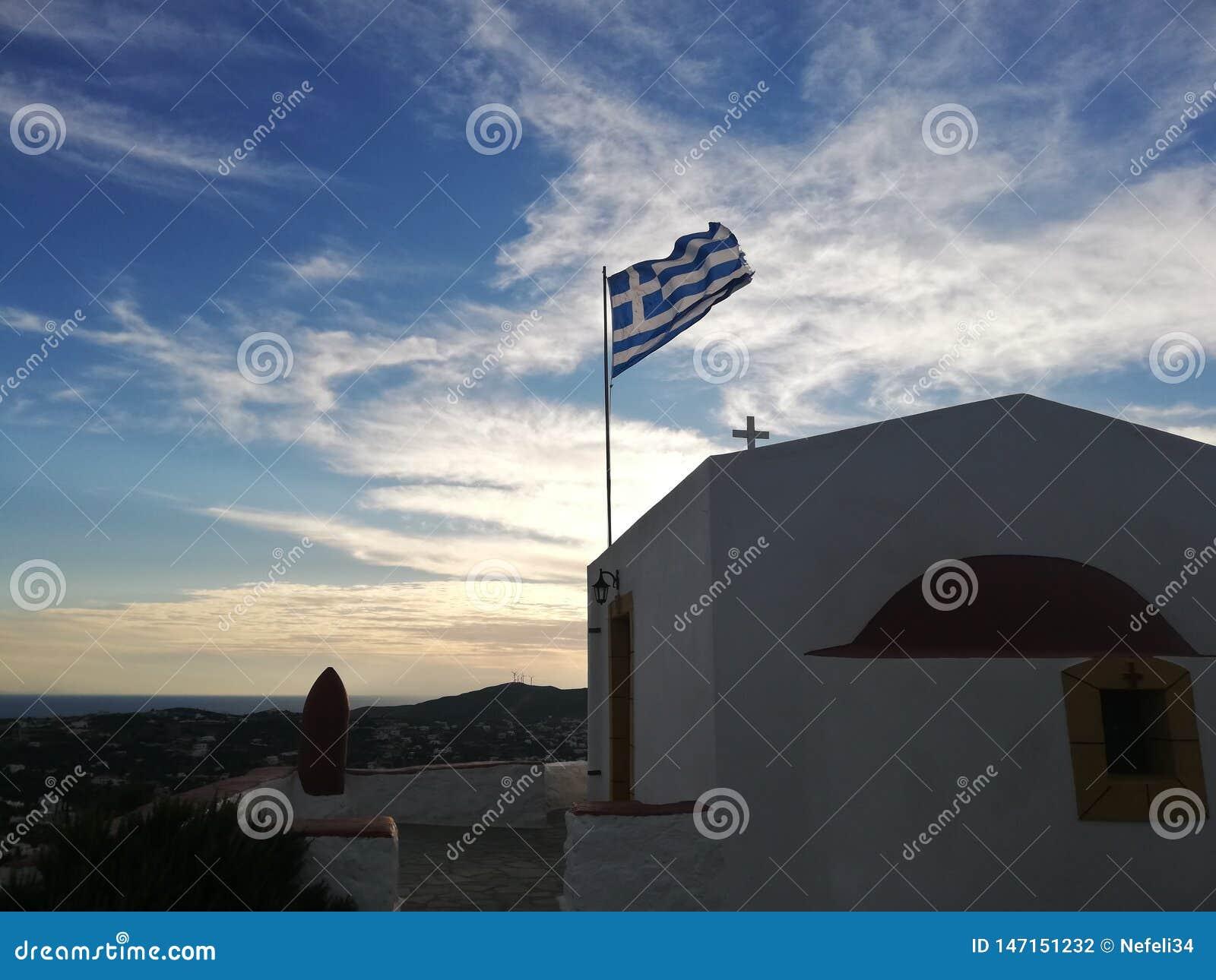 Iglesia griega y bandera con el cielo