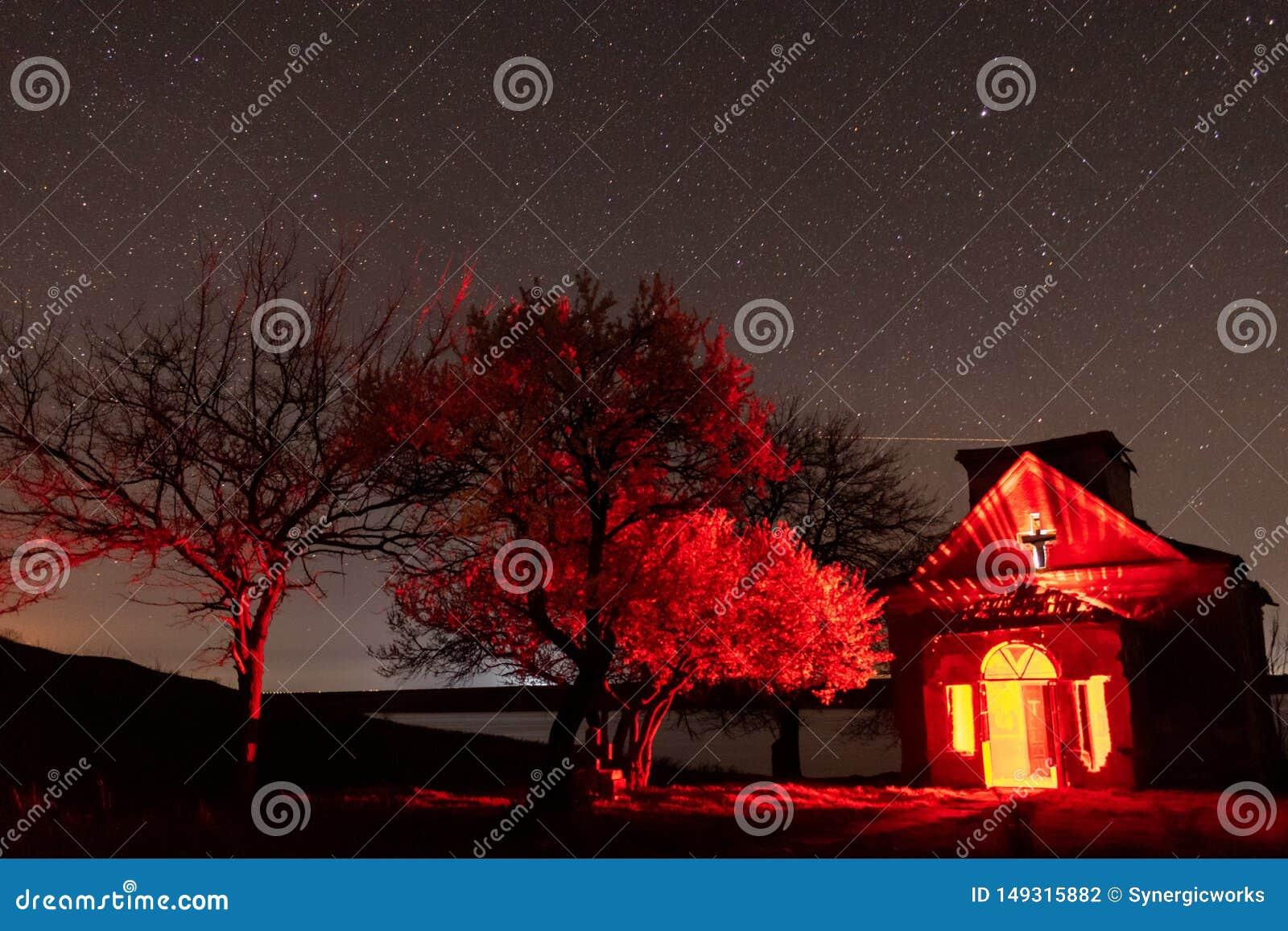 Igreja abandonada com interior claro vermelho e nightscape pr?ximo de floresc?ncia das ?rvores